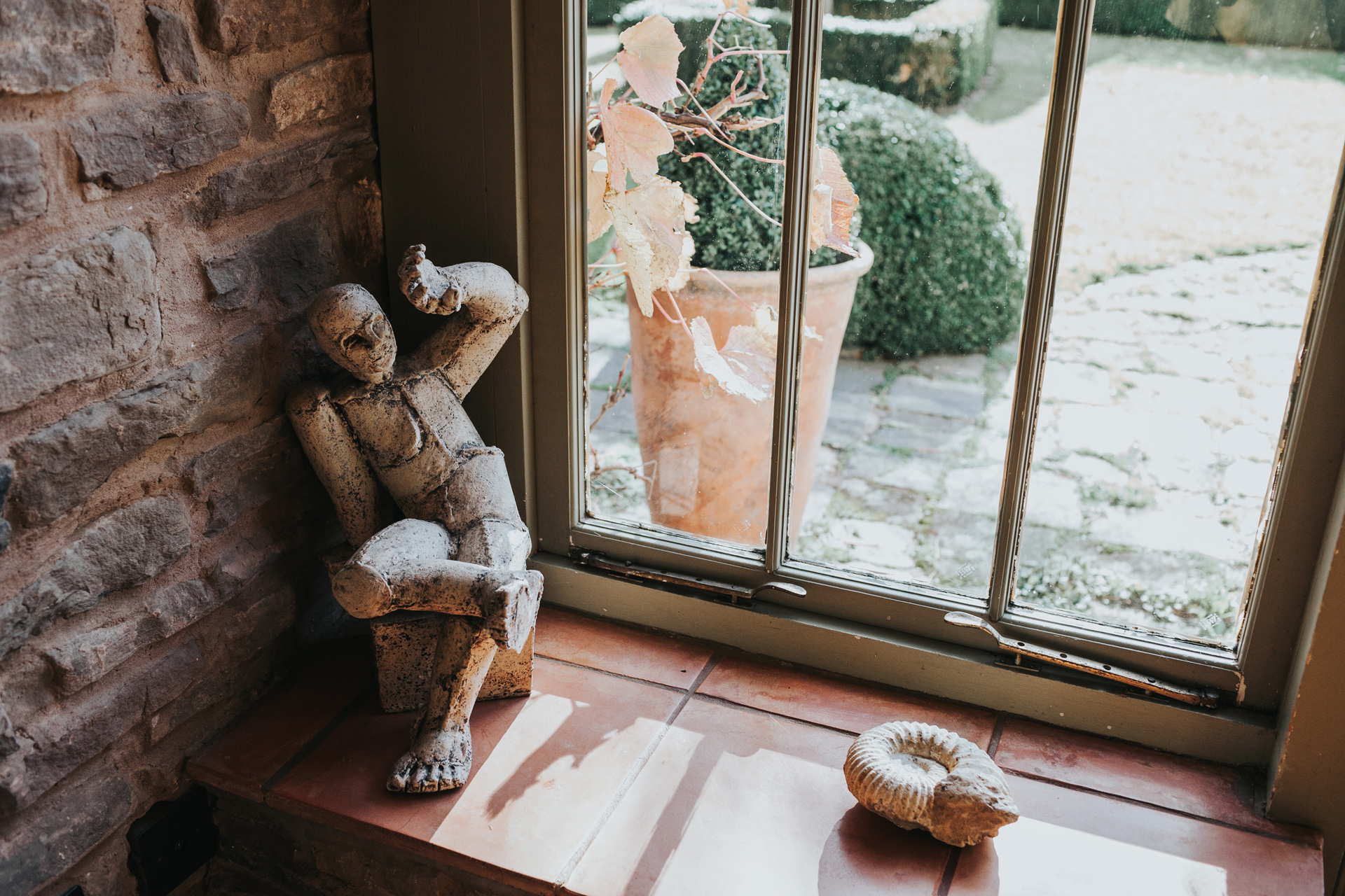Small statue of man shielding himself from the sun on the windowsill at Deswall Court.