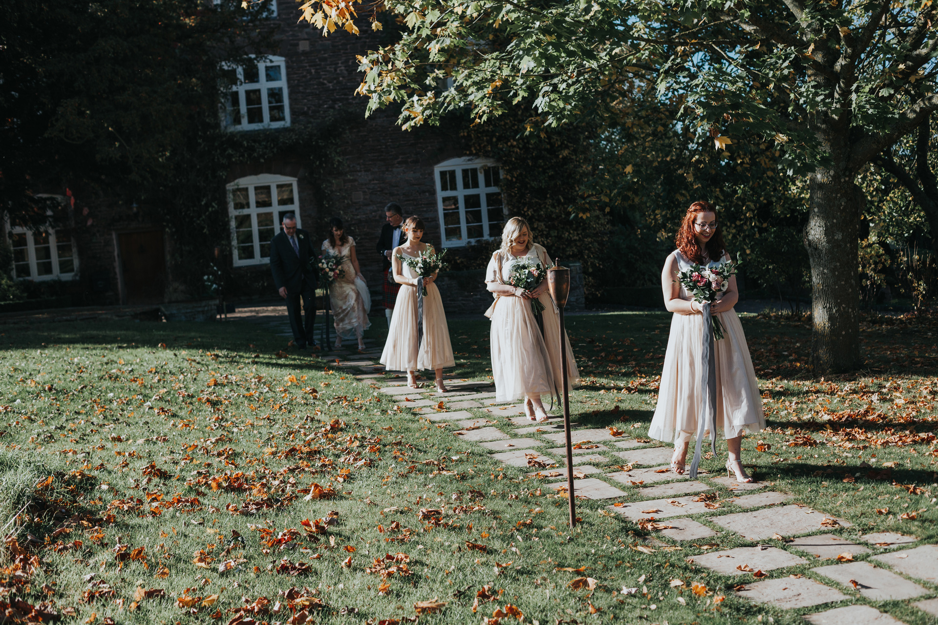 The bridesmaids lead the way across the lawn towards the ceremony room.