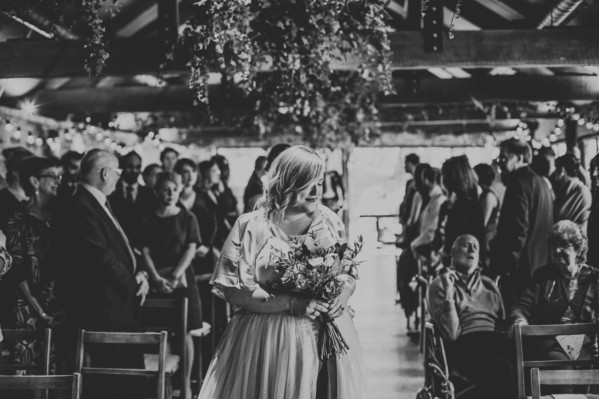Bridesmaid arrives at bottom of the aisle, photograph in black and white.