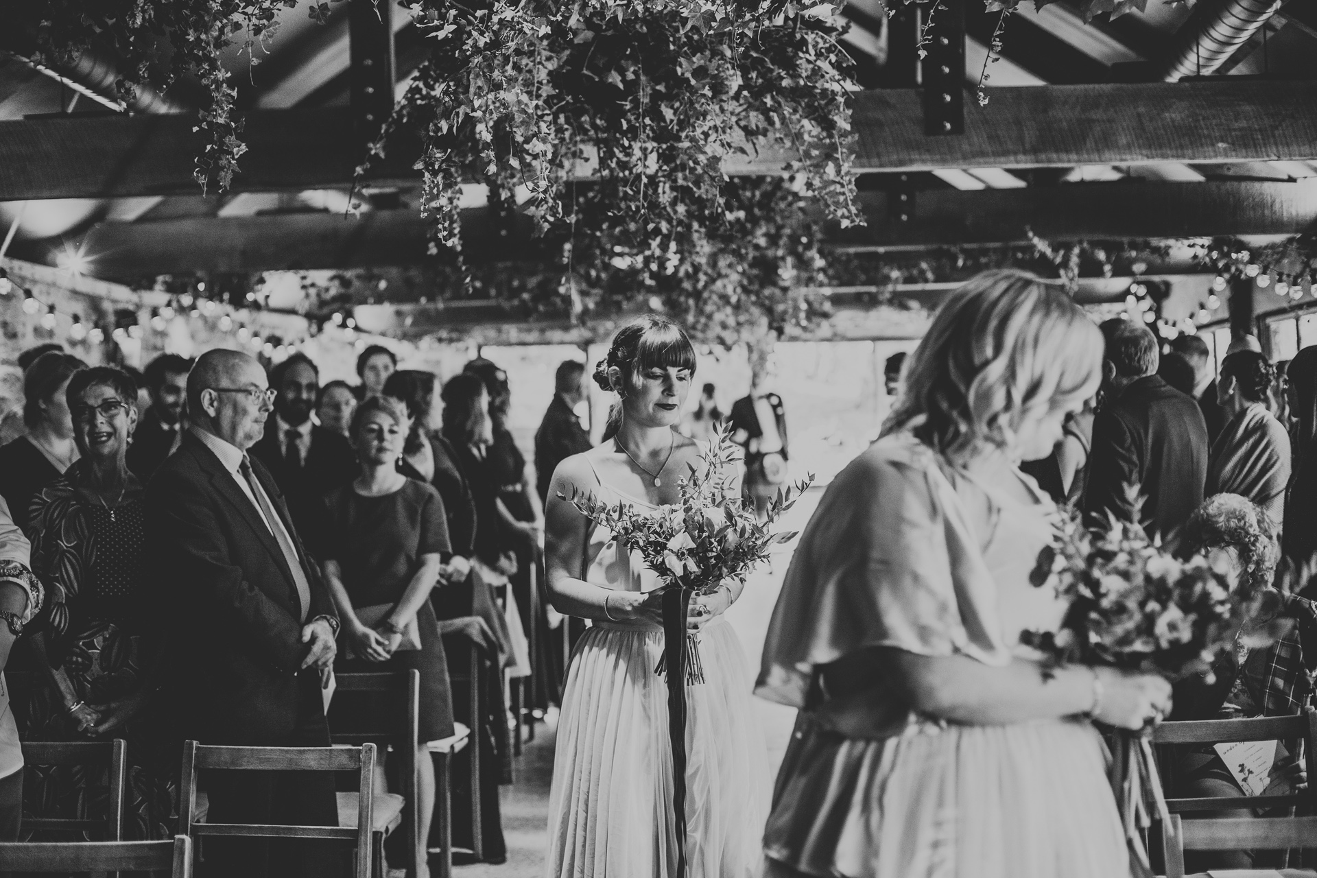 Third bridesmaid walks down the aisle. Photograph in black and white.