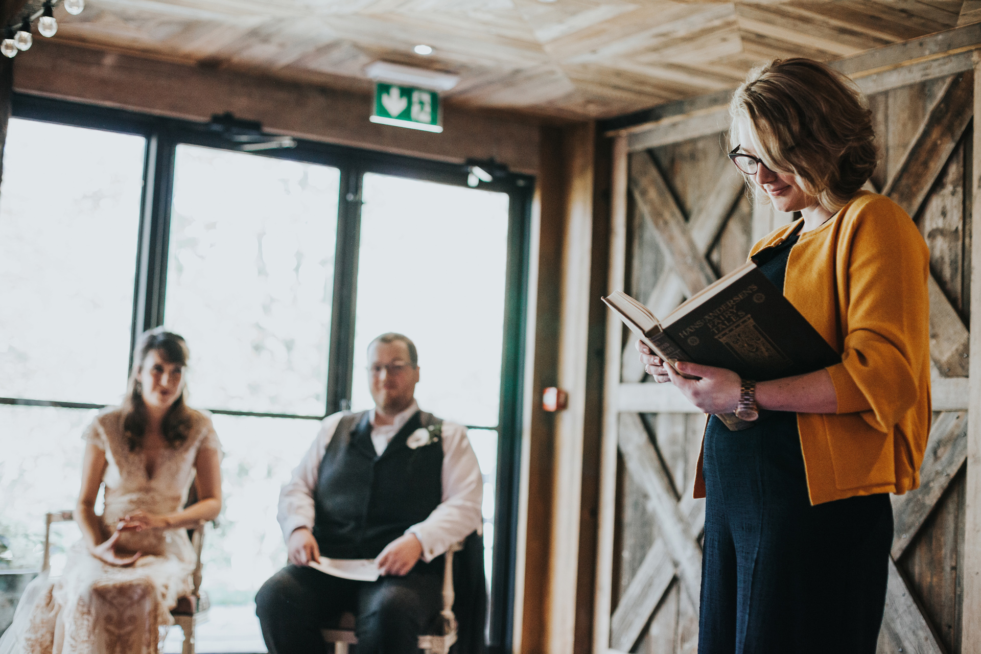 Celebrant and friend gives a reading to open the wedding ceremony, she is wearing a snazzy mustard cardigan.