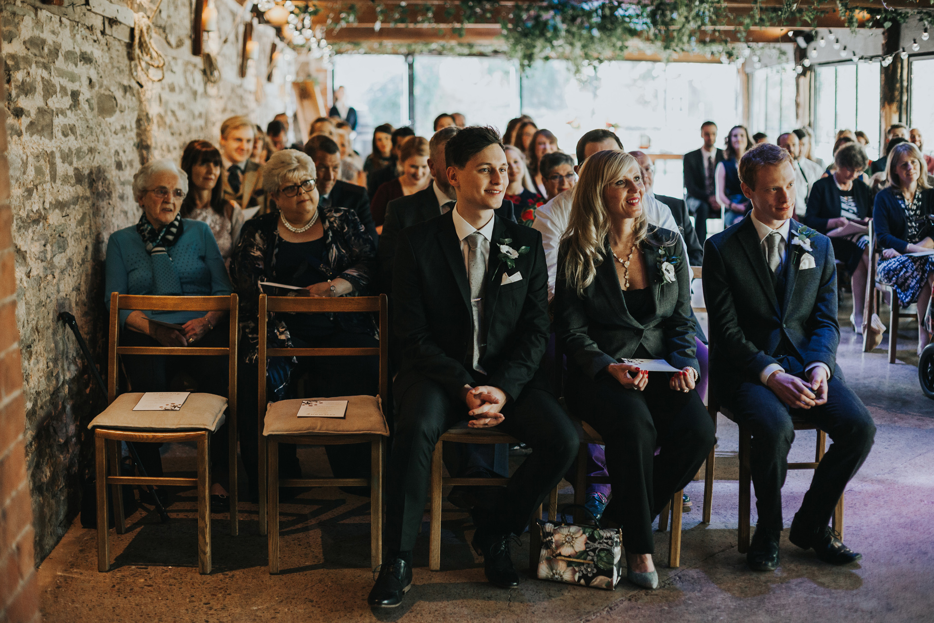 Wedding guests watch the couple saying theirs vows.