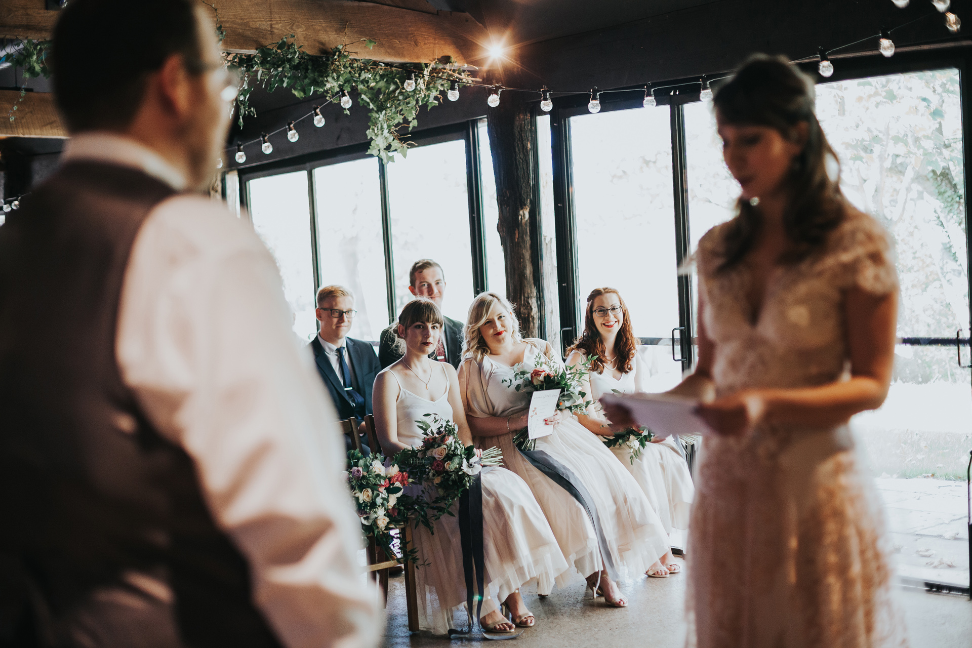 Bridesmaids watch couple say their vows.