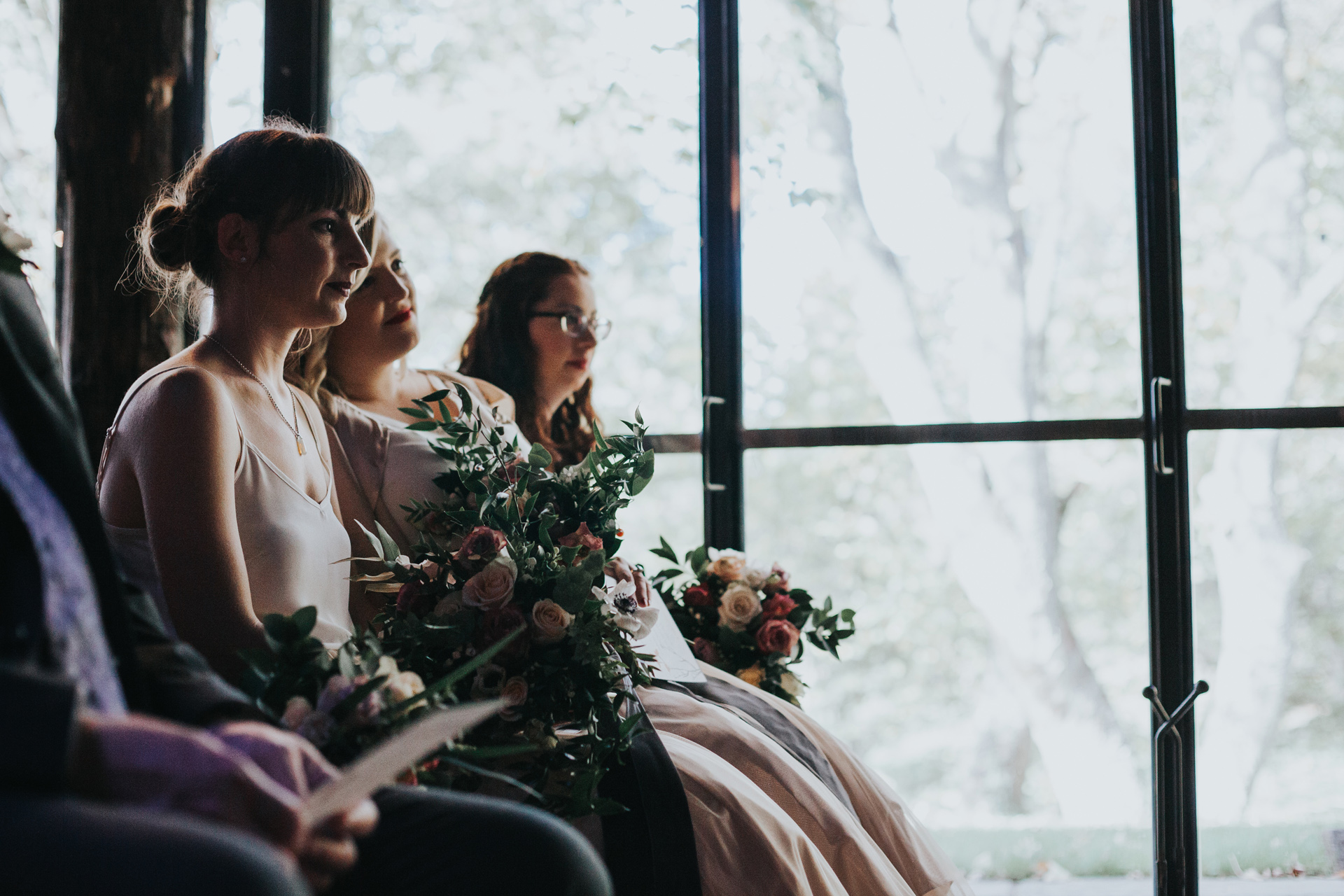 Bridesmaid sits in the shadows.