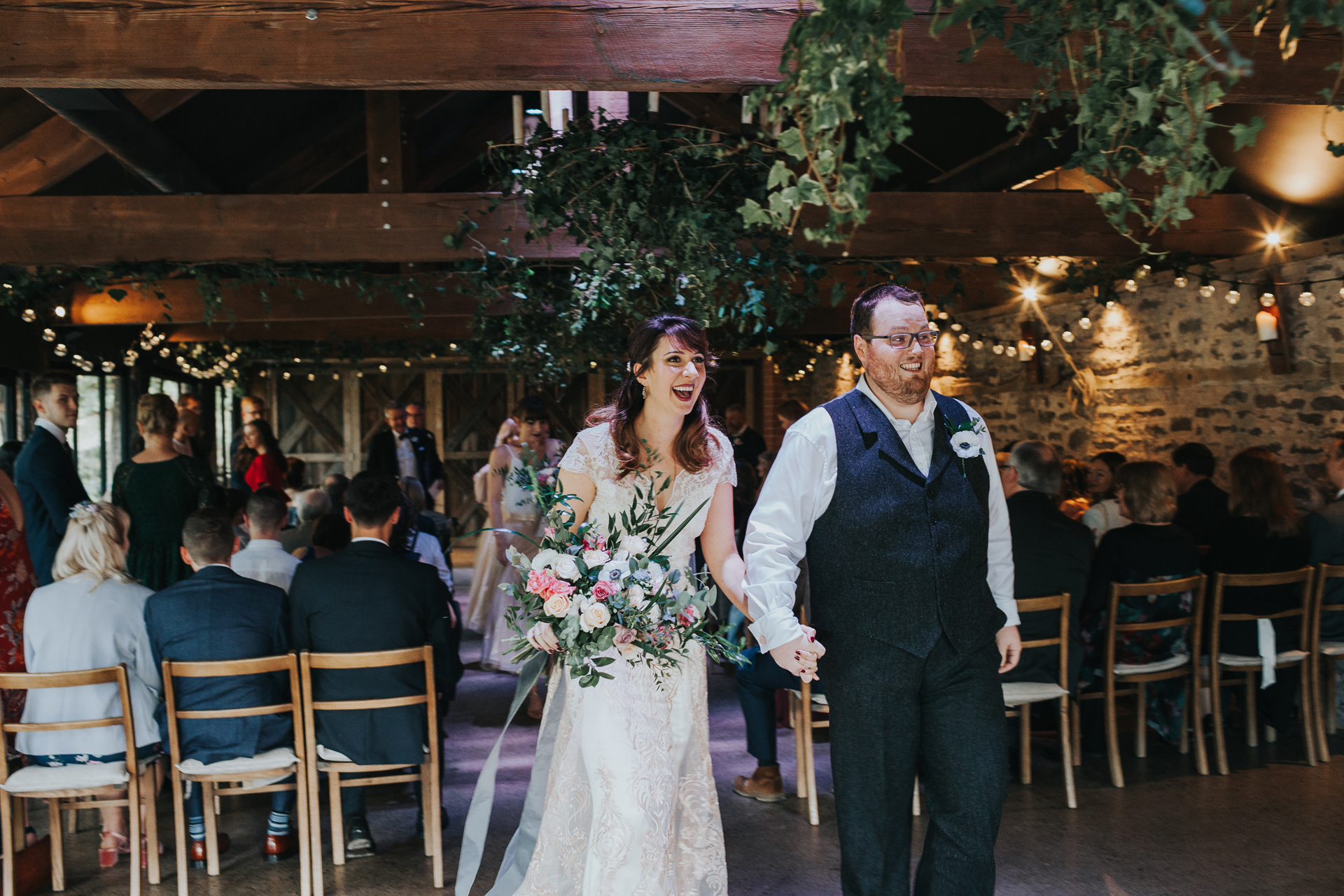 Bride and Groom exit the aisle at Dewsall Court