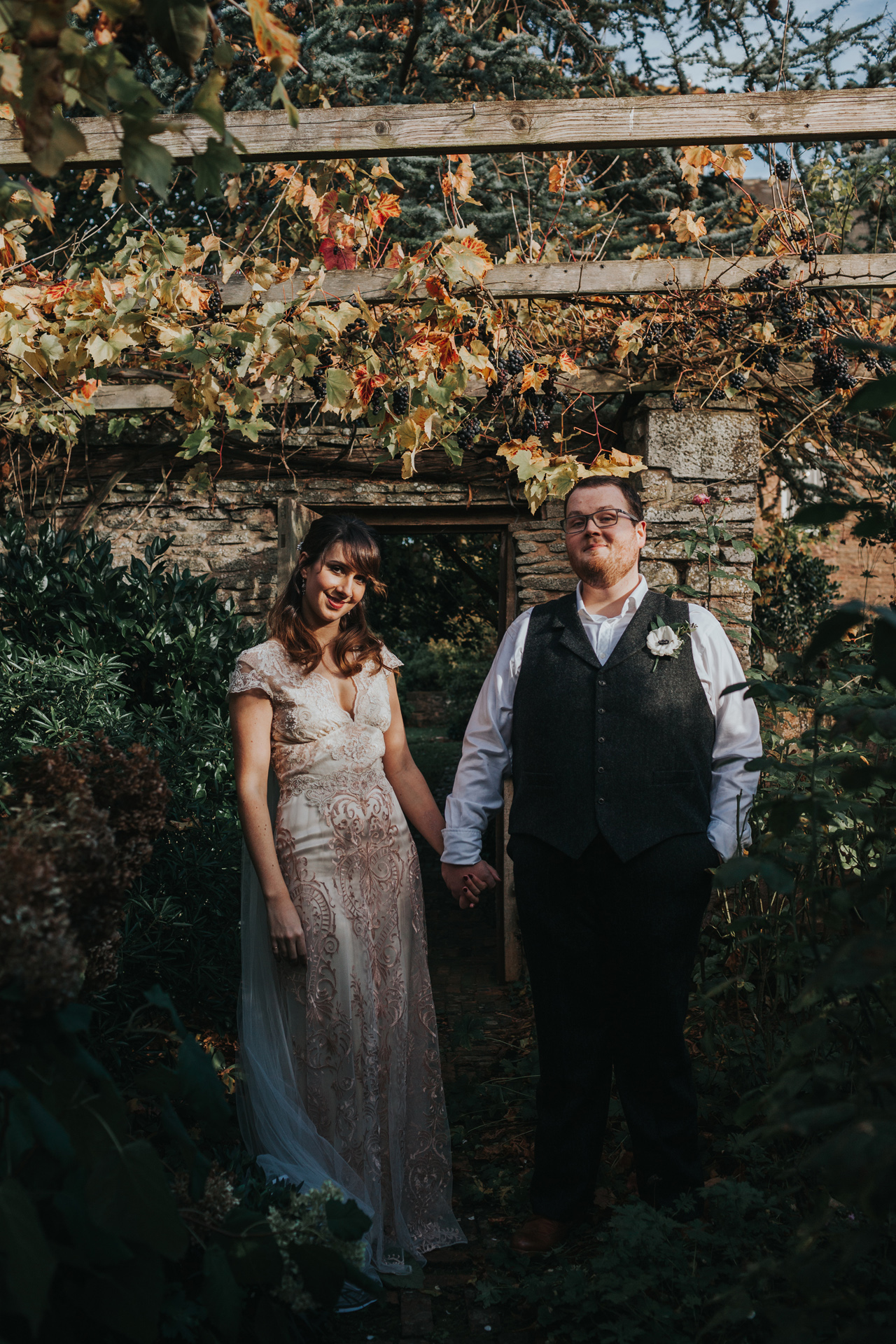 Portrait of couple standing in vineyard at Dewsall Court.