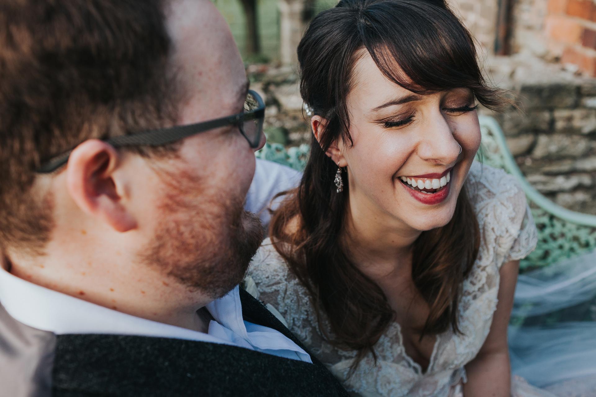 Bride laughs as groom whispers something in her ear.