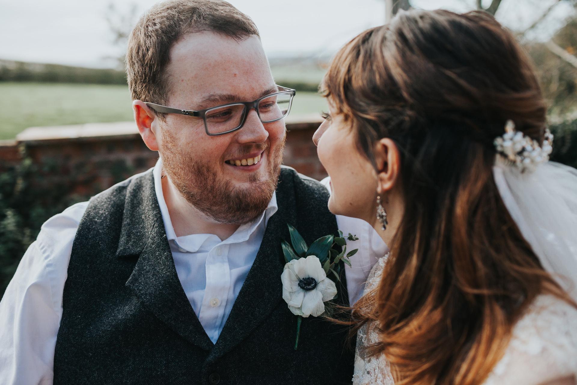 Groom smiling at bride.
