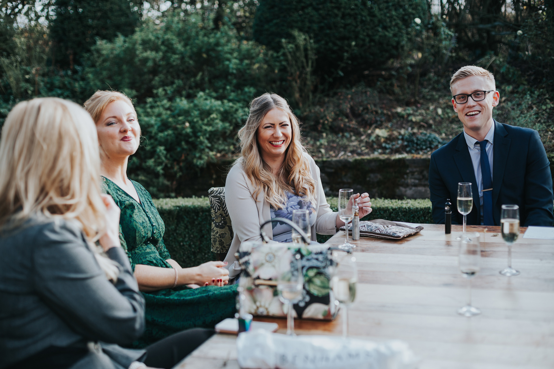 Wedding Guests sitting at table in garden laughing at Dewsall Court.