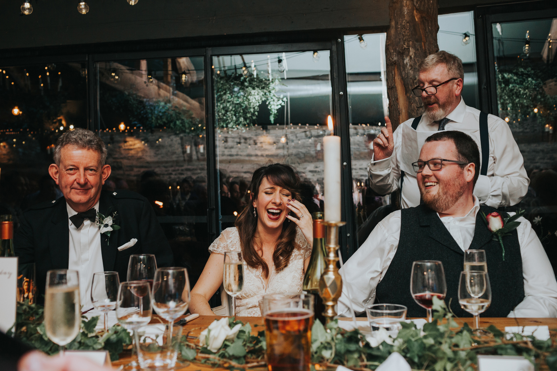 Father of the groom gives his speech as bride cries laughing.