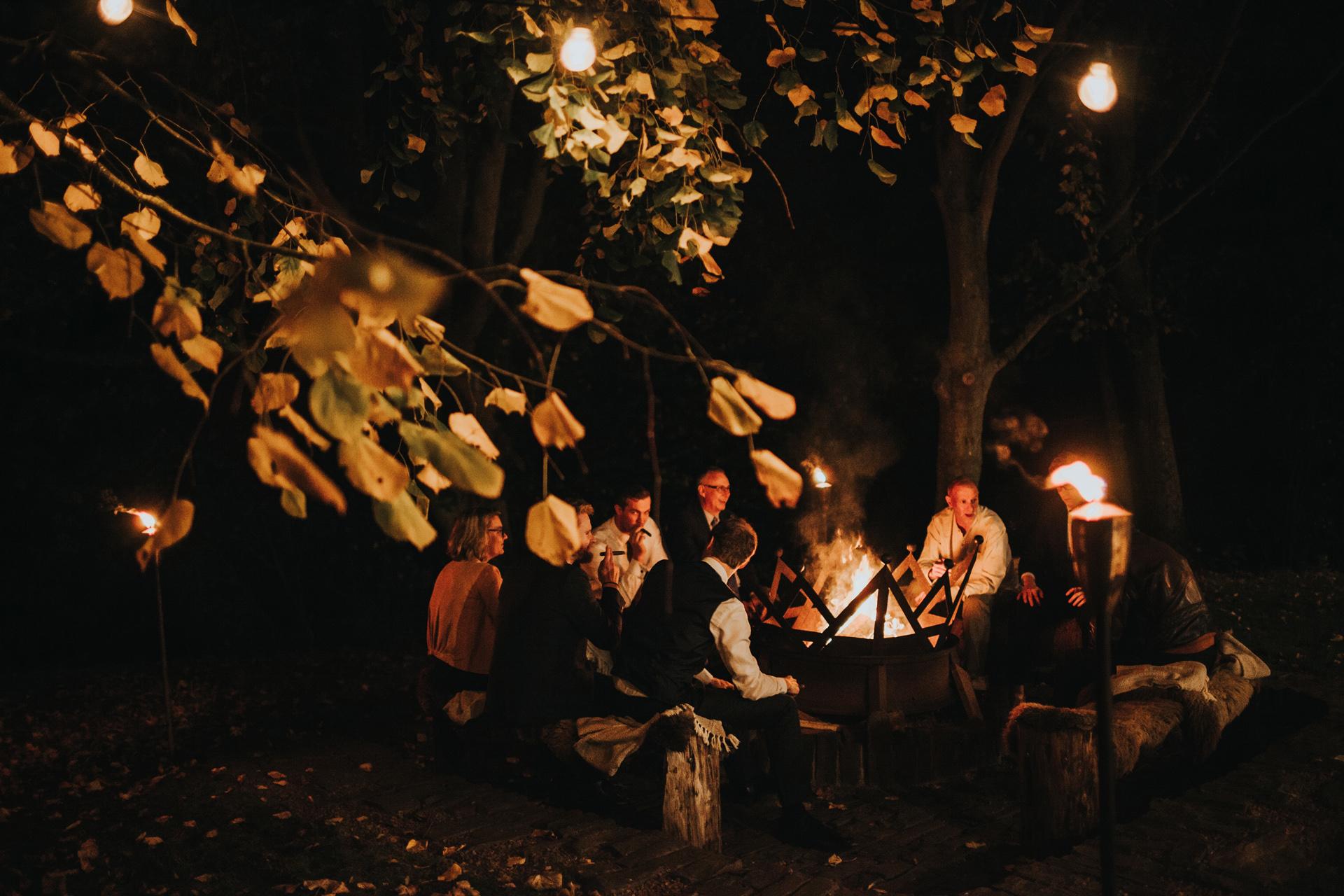 Wedding guests around camp fire.