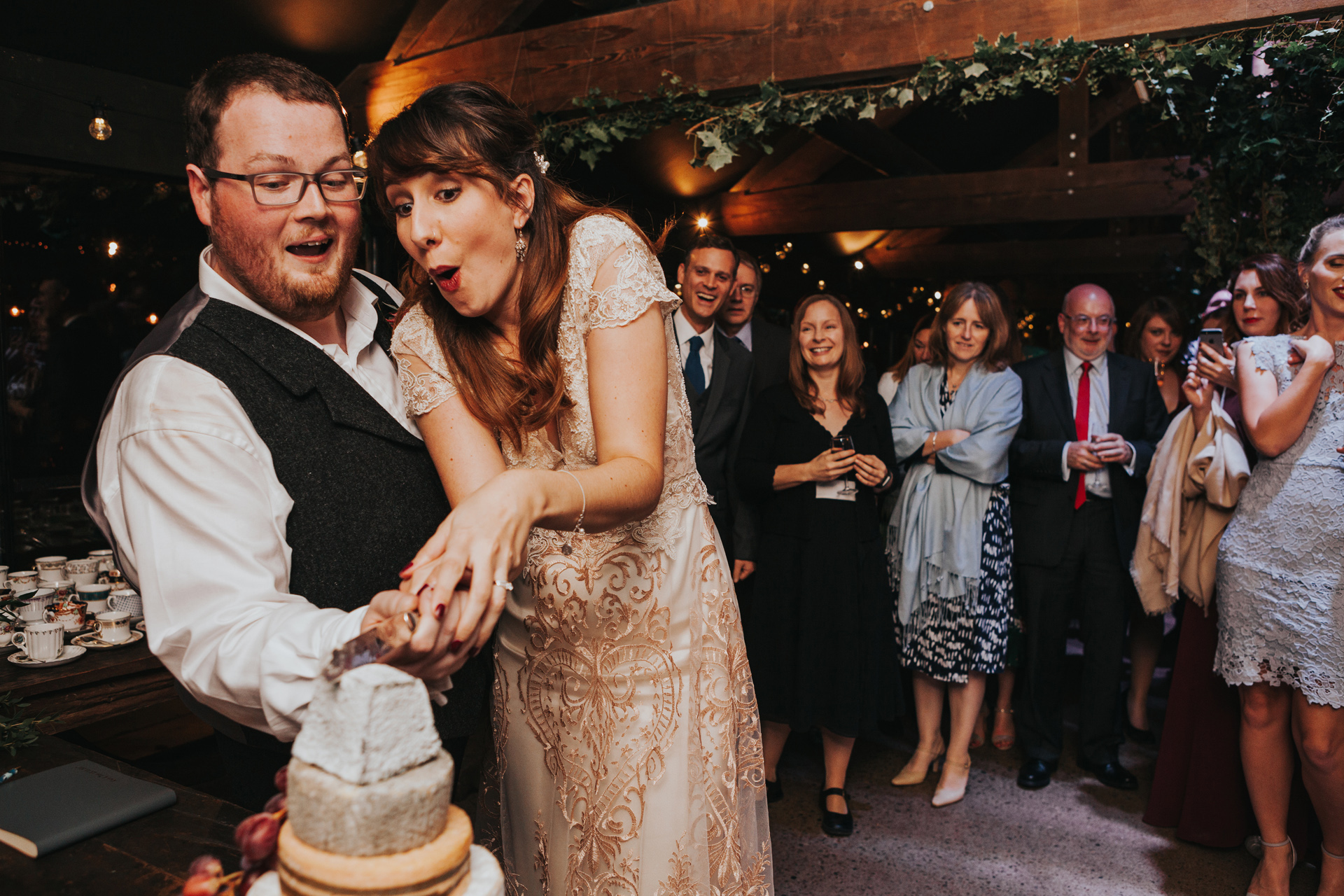 Bride and Groom cut cake with guests in background.
