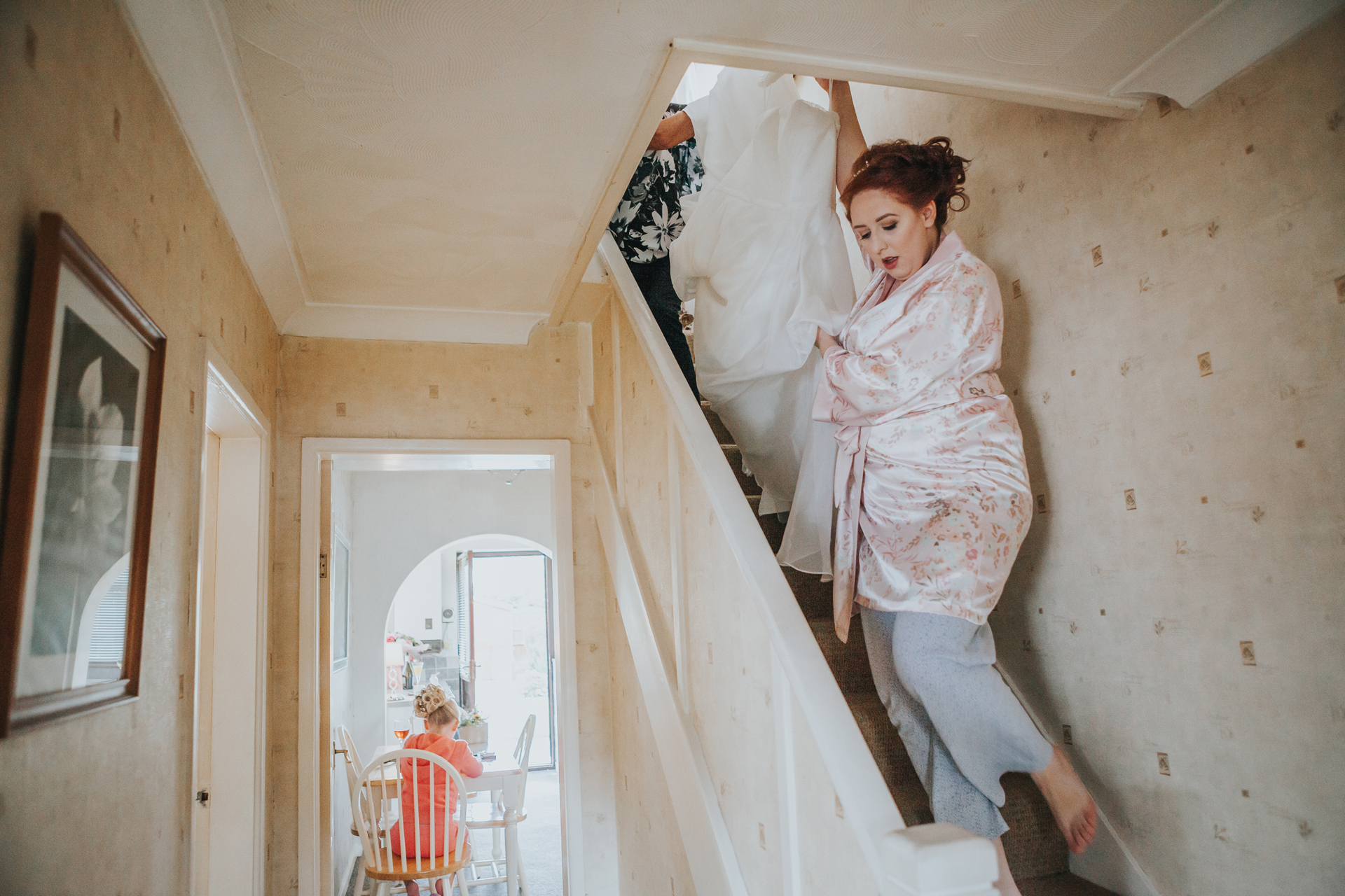 Bride bringing her dress down the stairs, bridesmaid waits in kitchen.