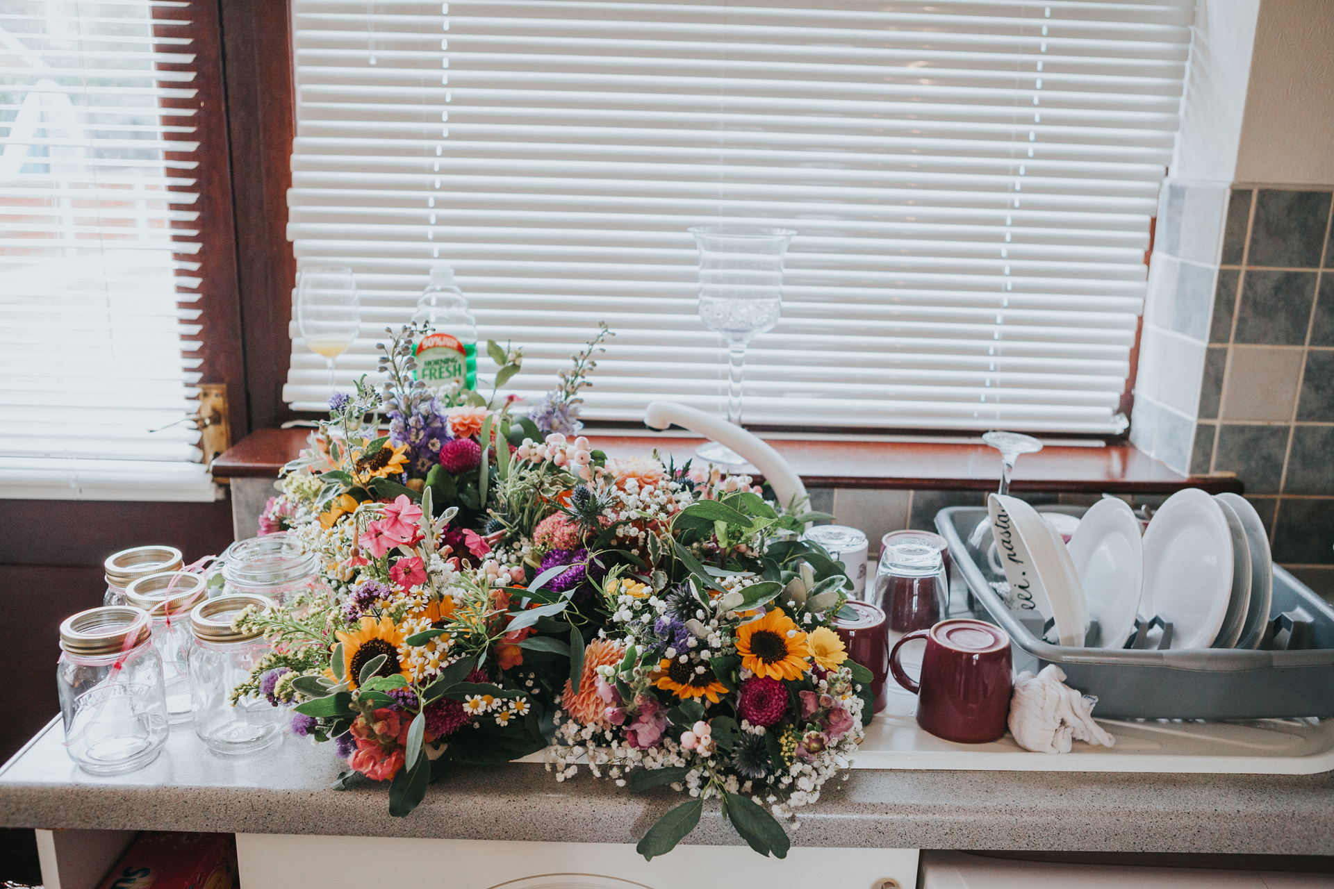 Flowers standing in the sink next to the drying dishes.