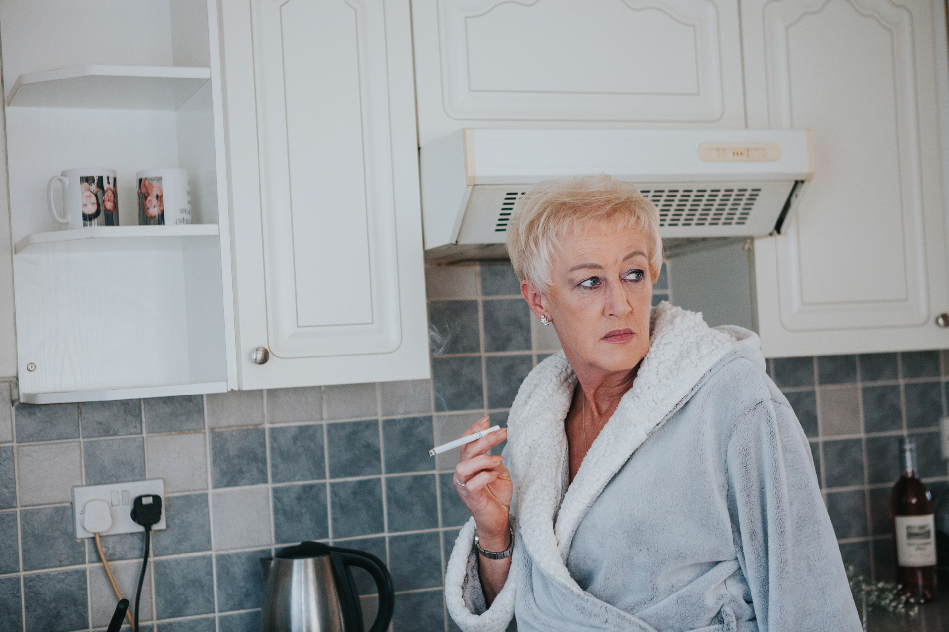 Mother of the bride having a fag in the kitchen.