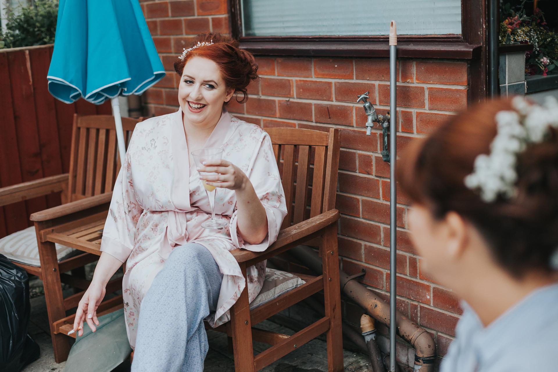 Bride having a fag and bucks fizz break in the kitchen.