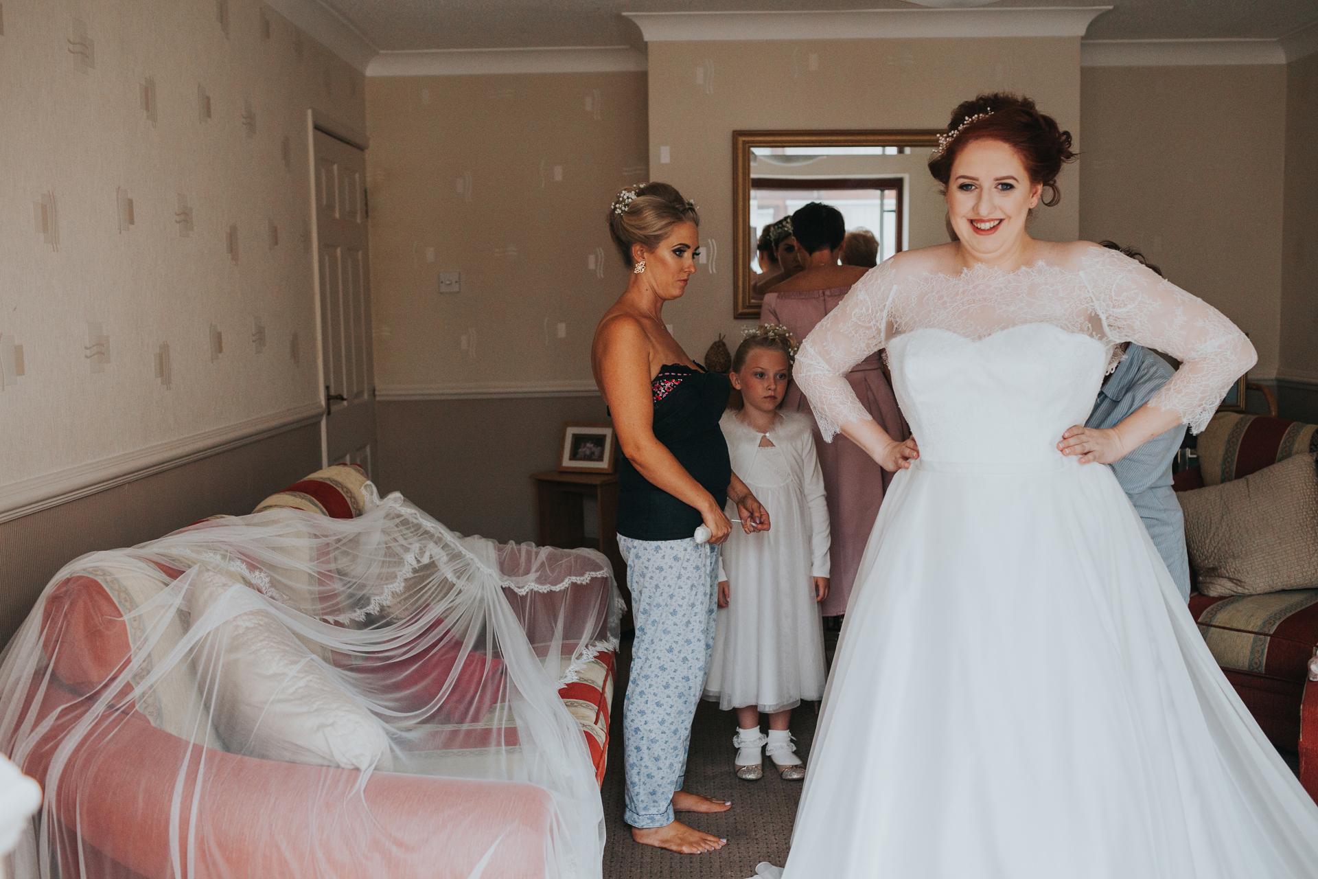 Bride stood next to veil on sofa.
