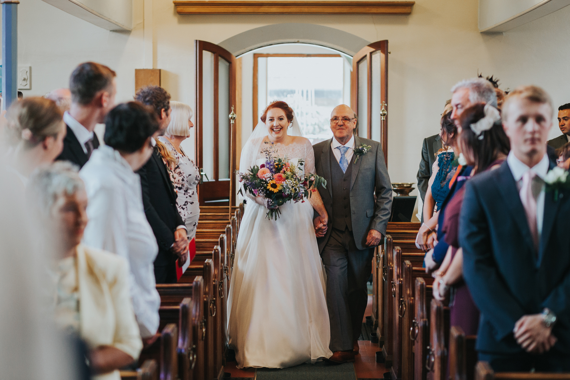 Bride walks down the aisle with her father.