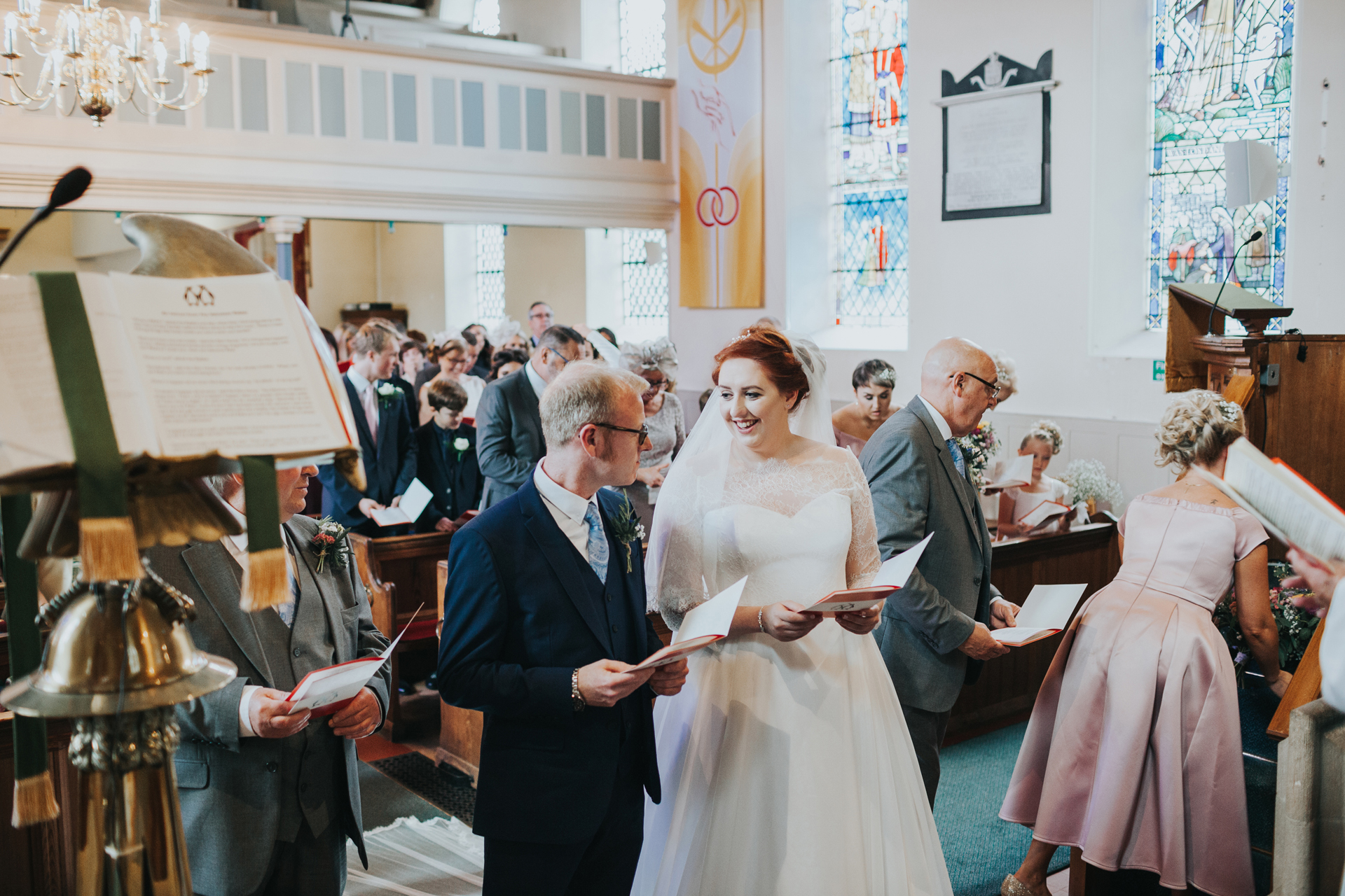 Bride and groom look at each other smiling over their hymn sheets.