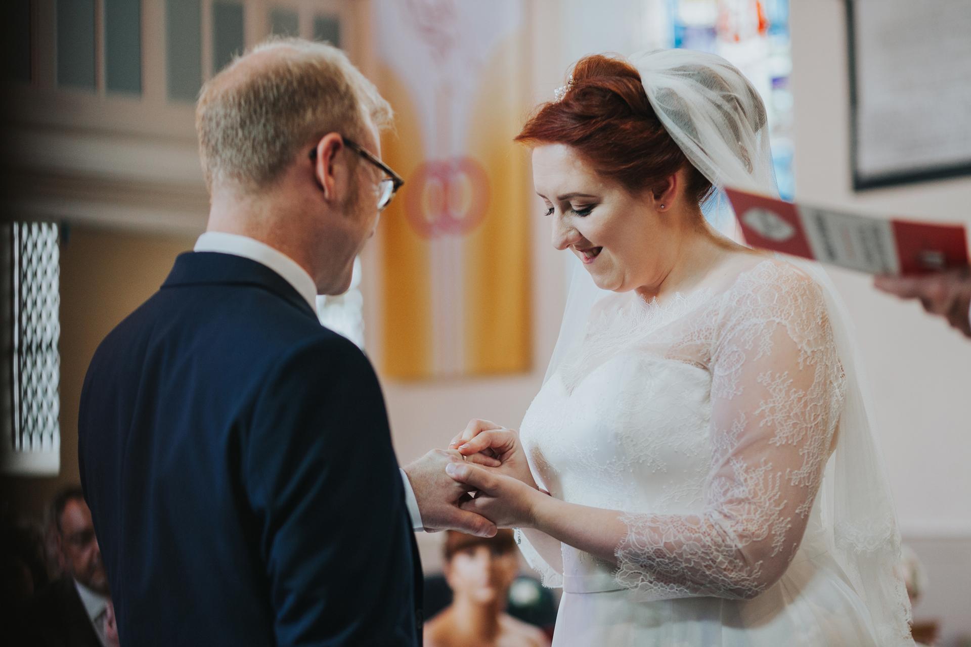 Bride puts ring on grooms finger.