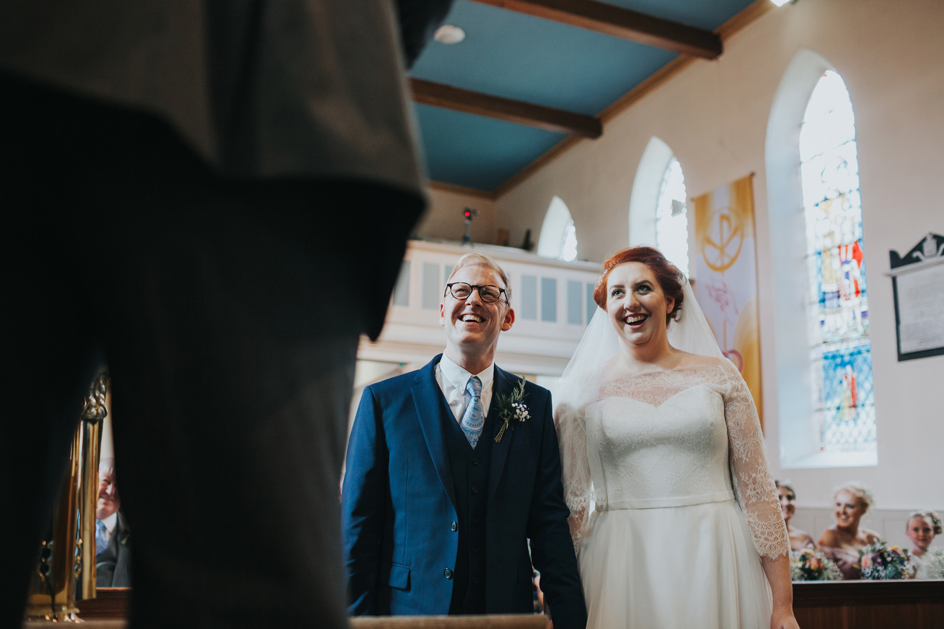 Bride and groom look on smiling as their friend reads.