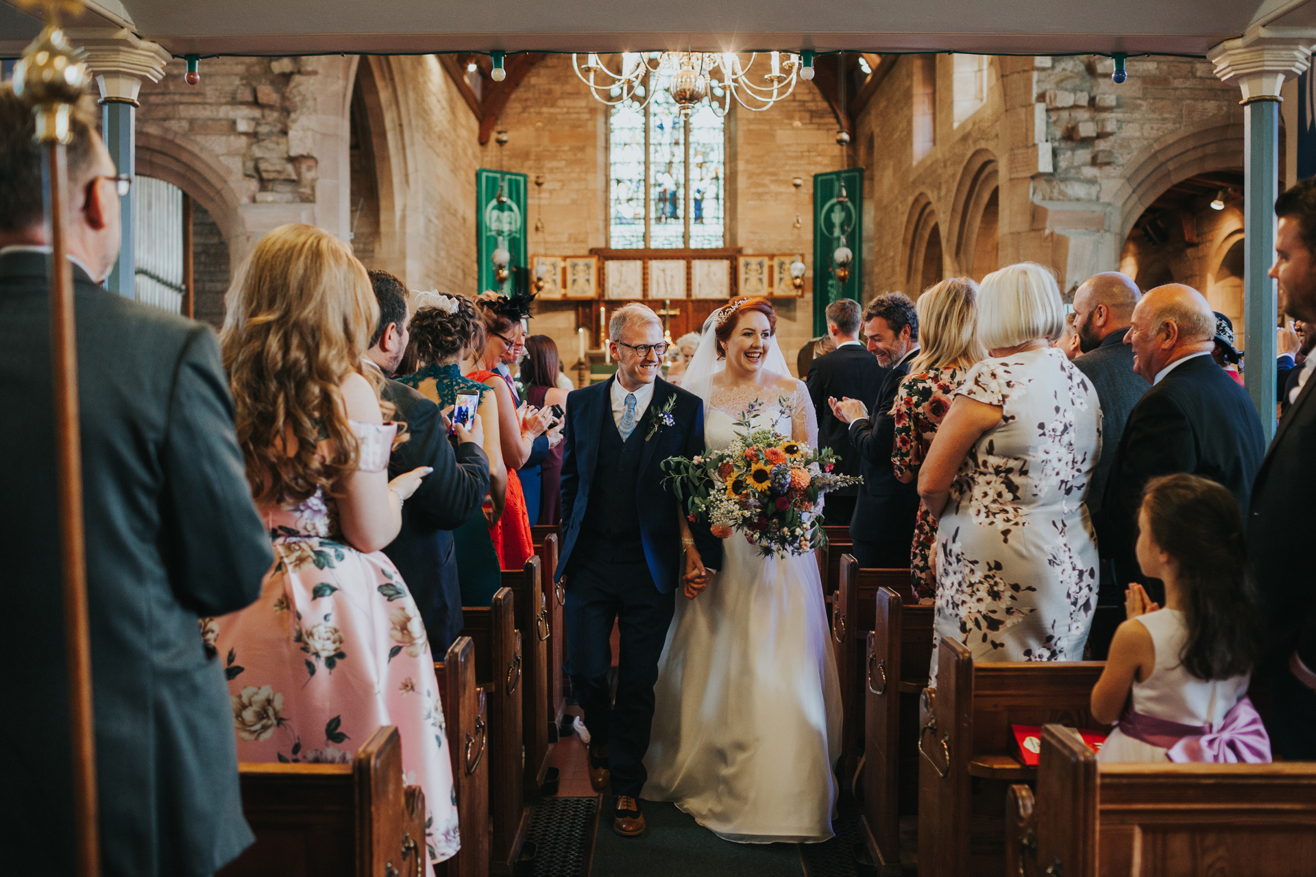 Bride and groom make their way down the aisle as man and wife.