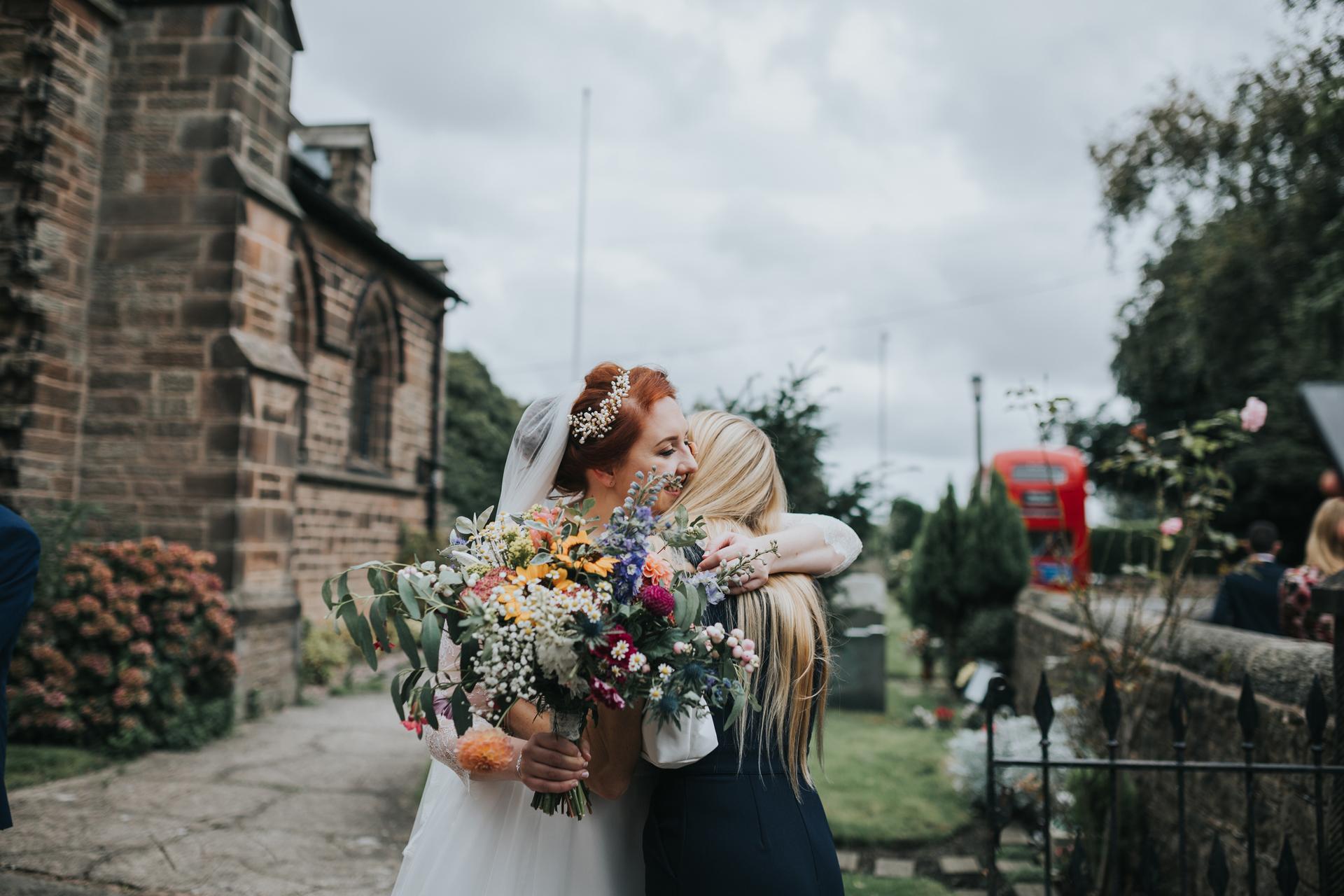 Bride hugs friend.