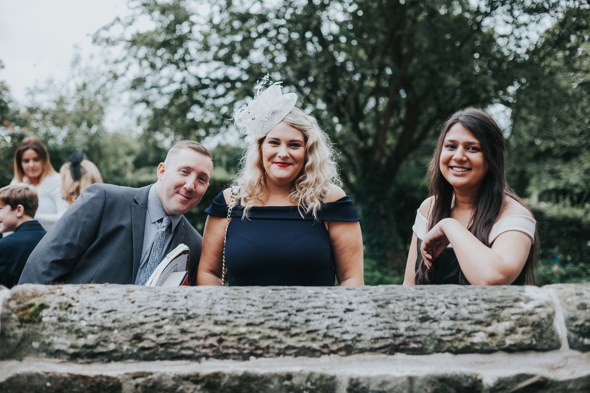 Guests smile over church wall.