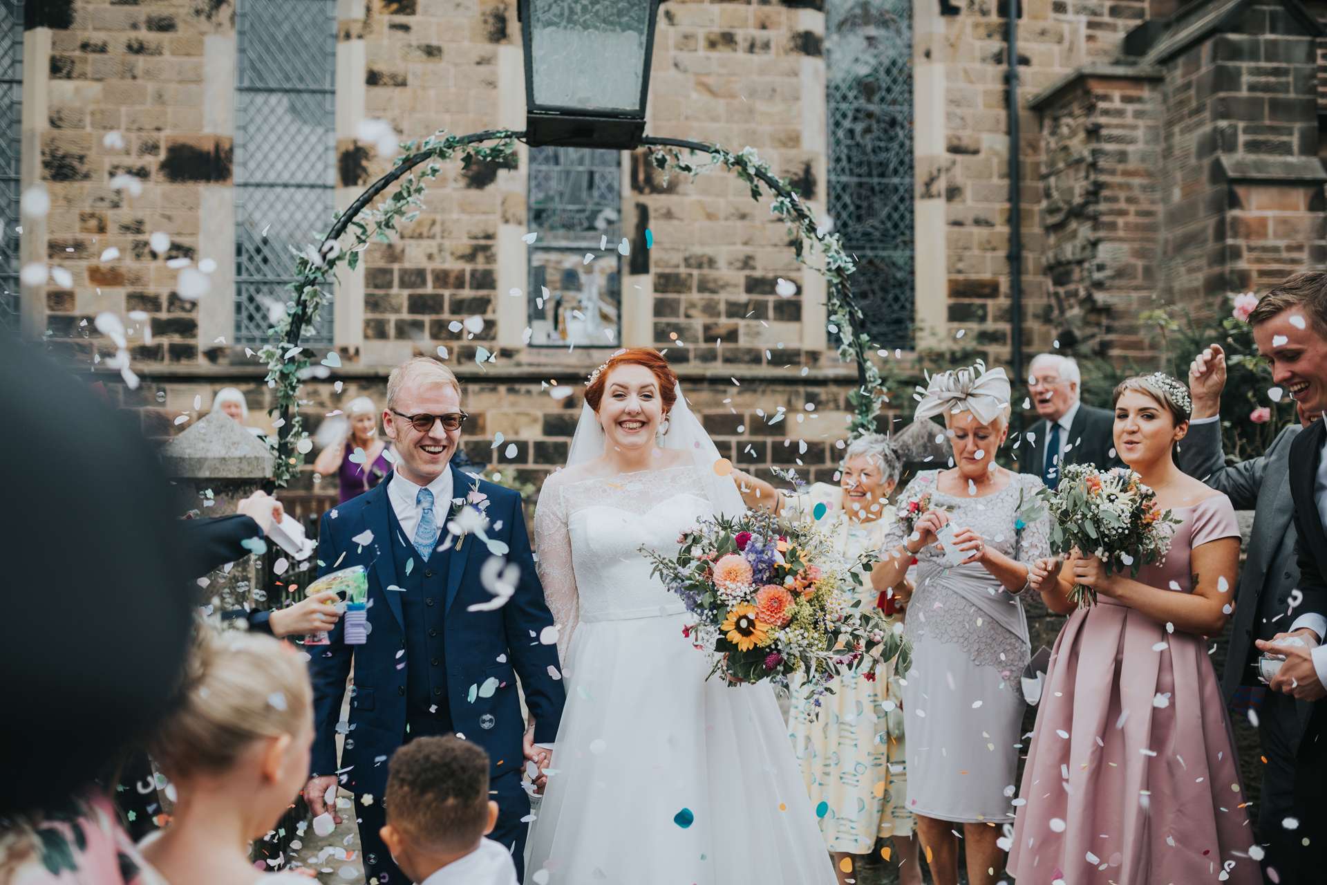 Guests surround bride and groom as they throw confetti at them at St Thomas Church Liverpool