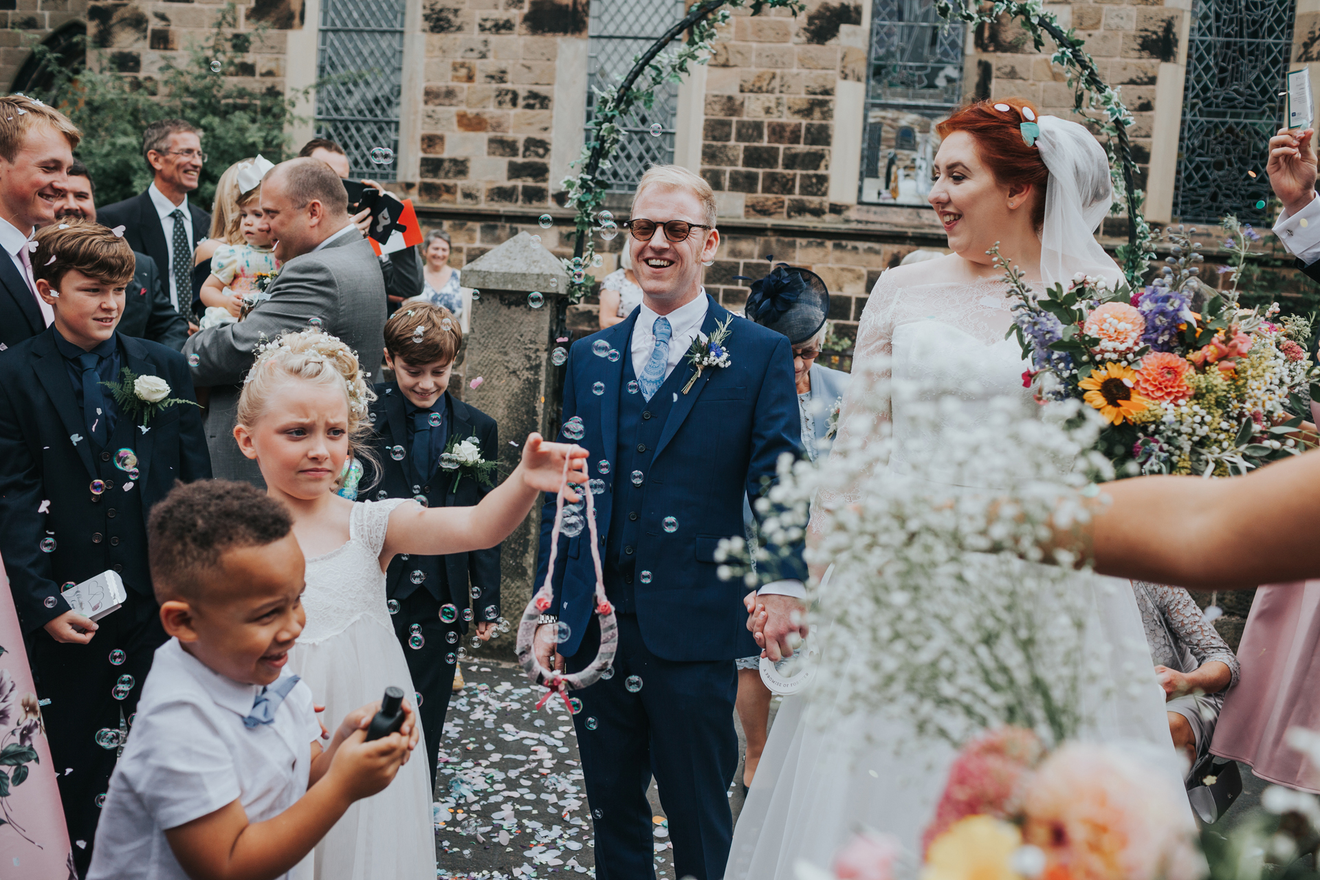 Confetti and bubbles surround bride and groom as they laugh.