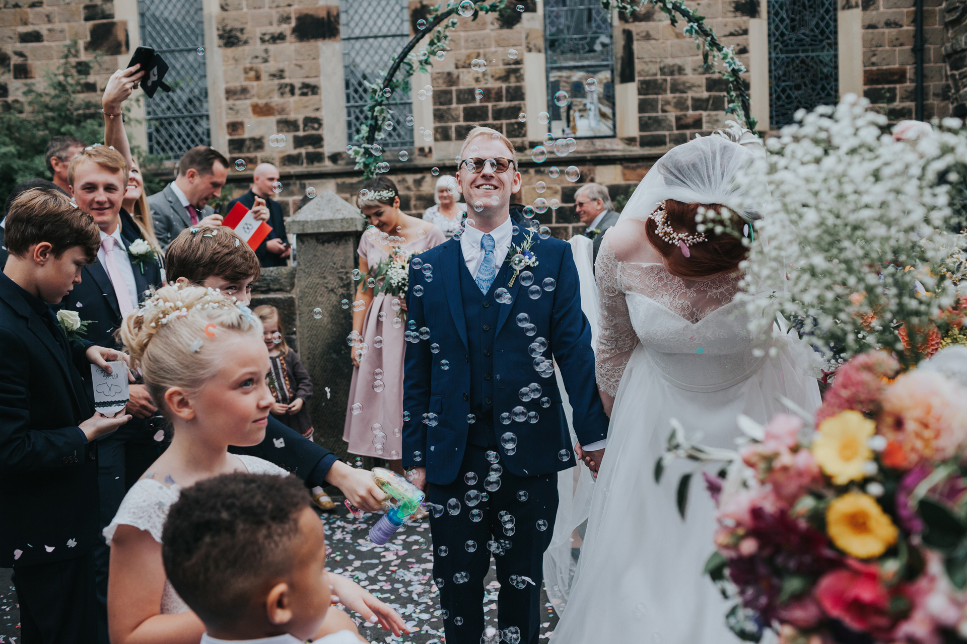 Bubbles, flowers and bride and groom as they exit St Thomas's Church, Liverpool.