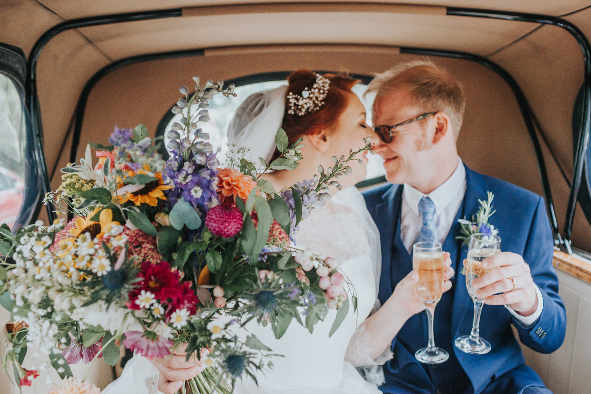 Bride and groom have a kiss in the back on the wedding car, focus on the brides bouquet.