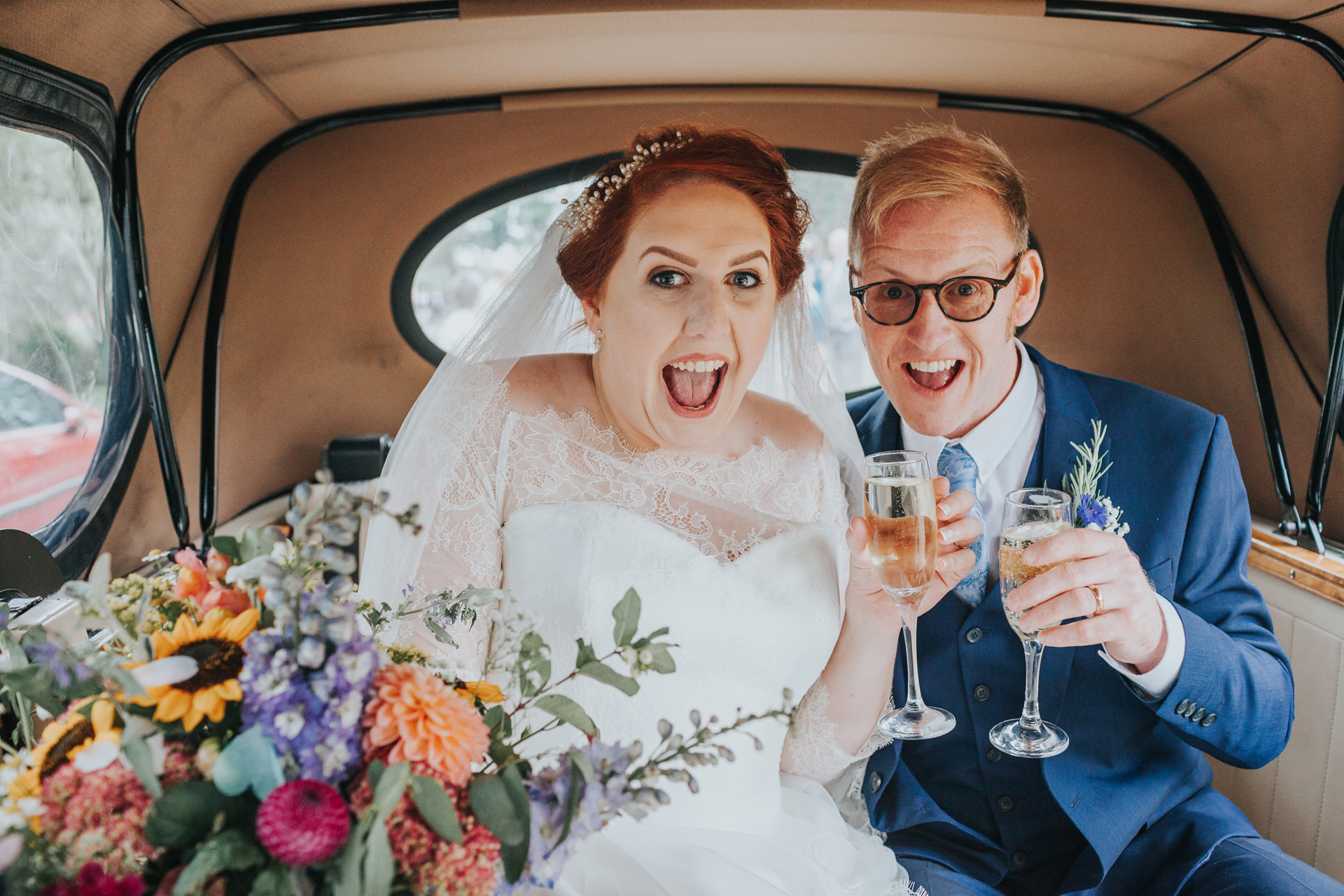 Bride and groom have excited faces in the back on the wedding car.