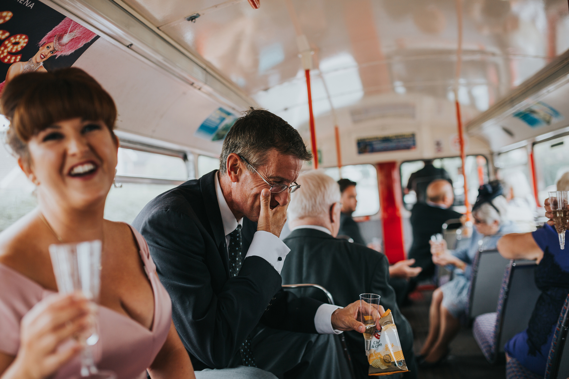 Guests laugh on the top deck of the wedding bus.