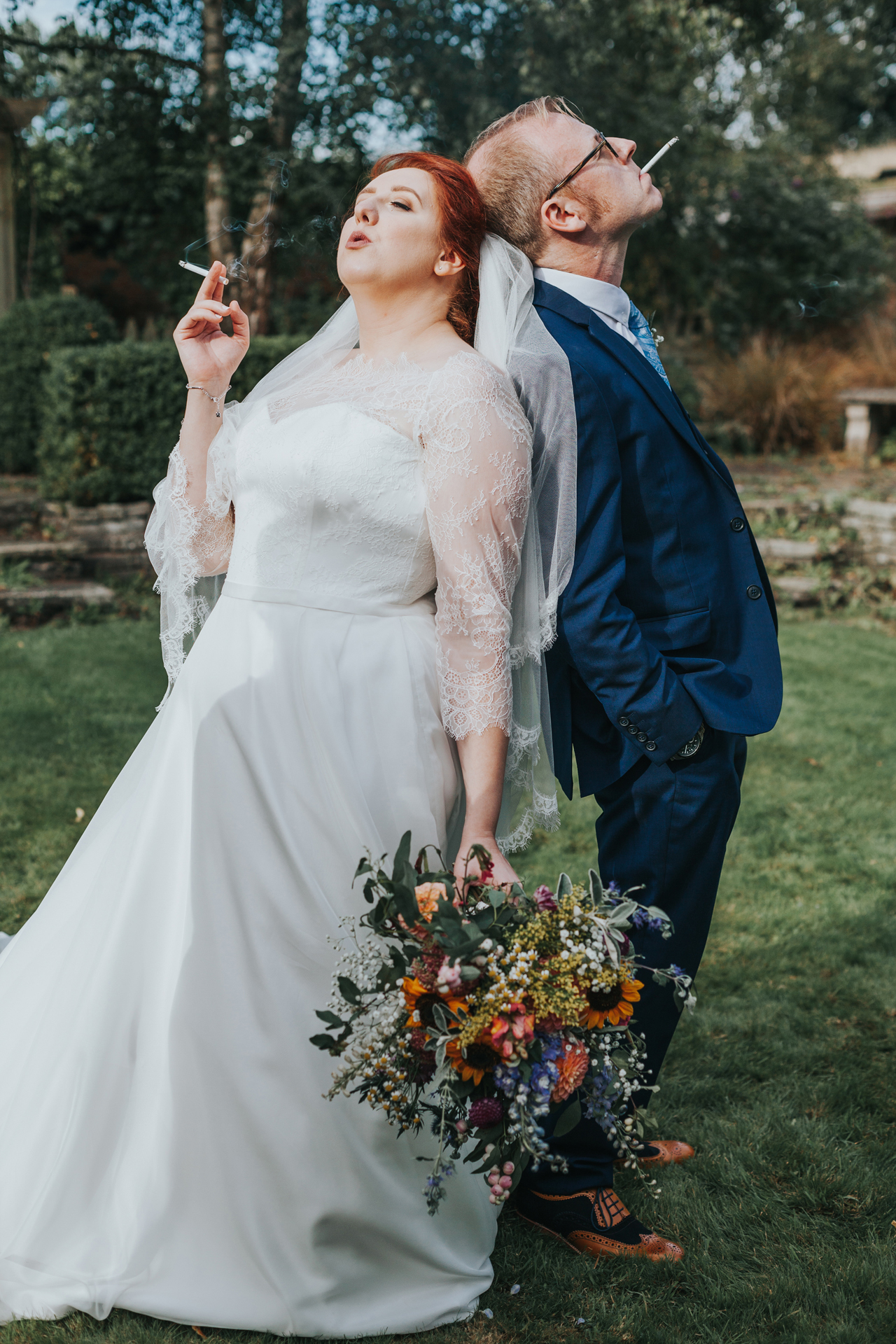 Bride and Groom posing back to back with their fags.