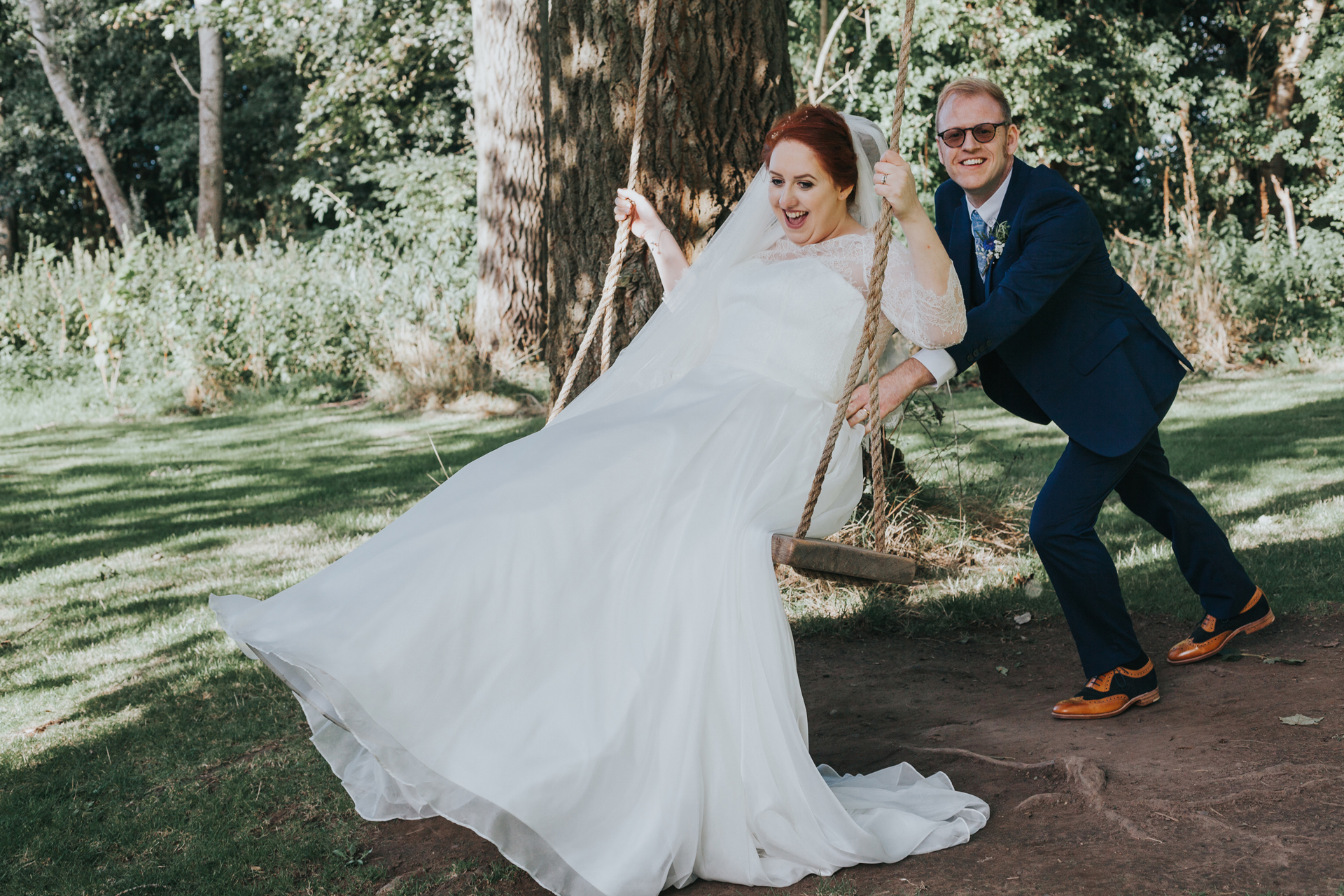 Groom pushes bride on swing at Trafford hall.