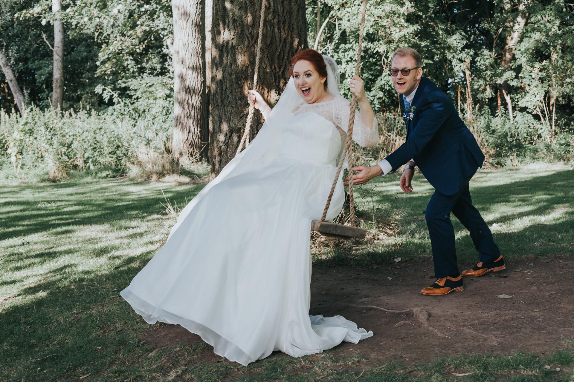 Groom pushes bride on swing.