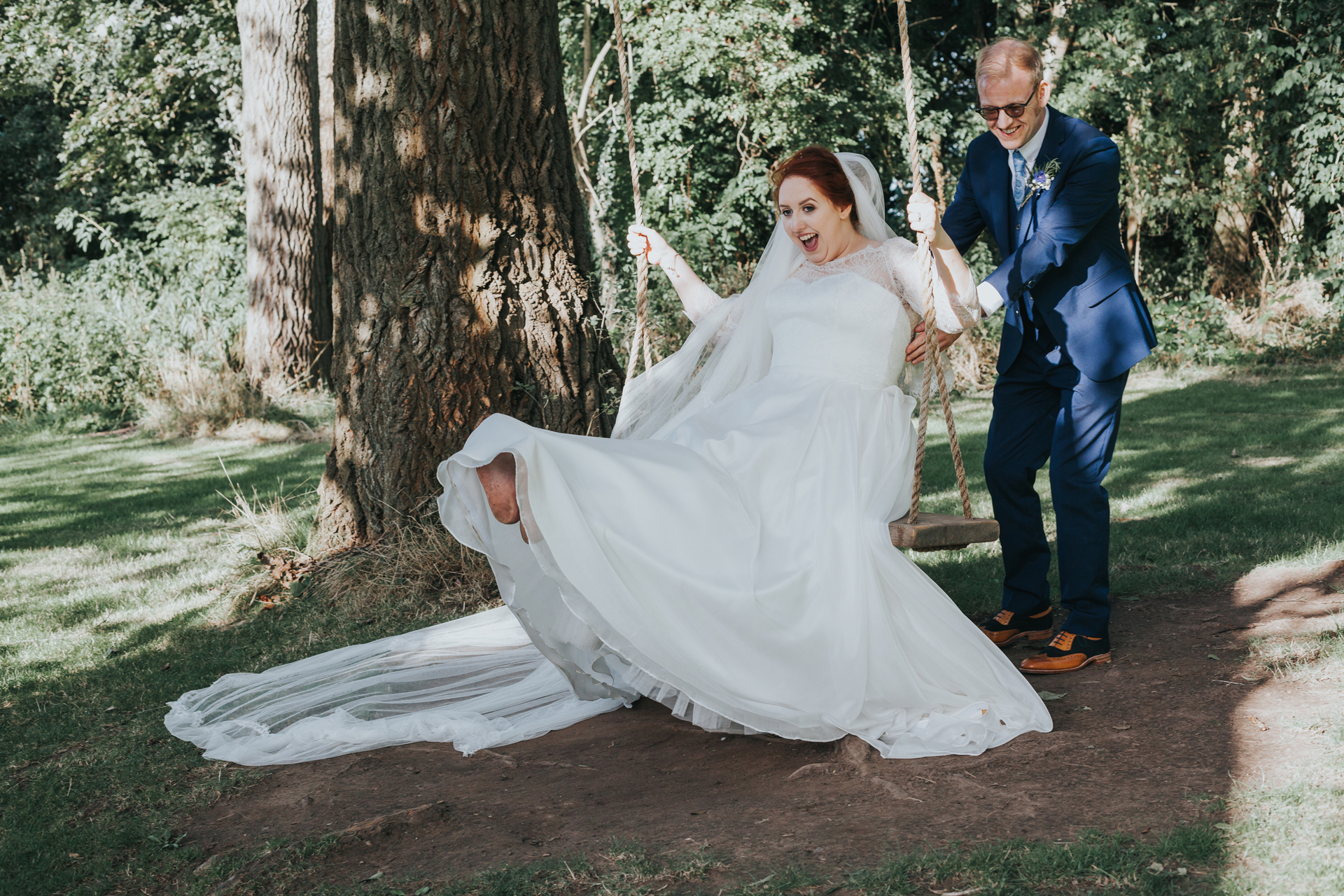 Bride and groom play on tree swing at Trafford Hall.