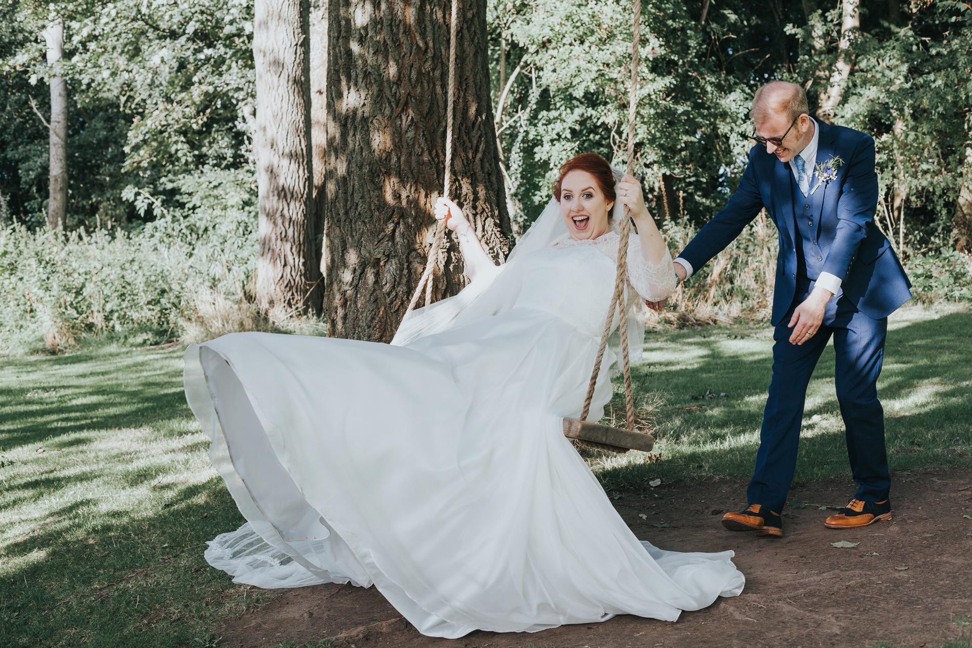 Bride and groom playing on swings.