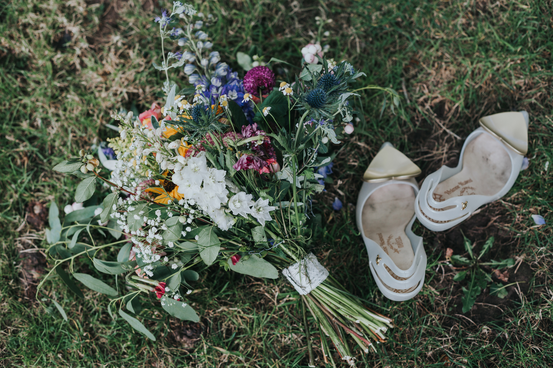 Brides flowers and shoes lying on the grass.