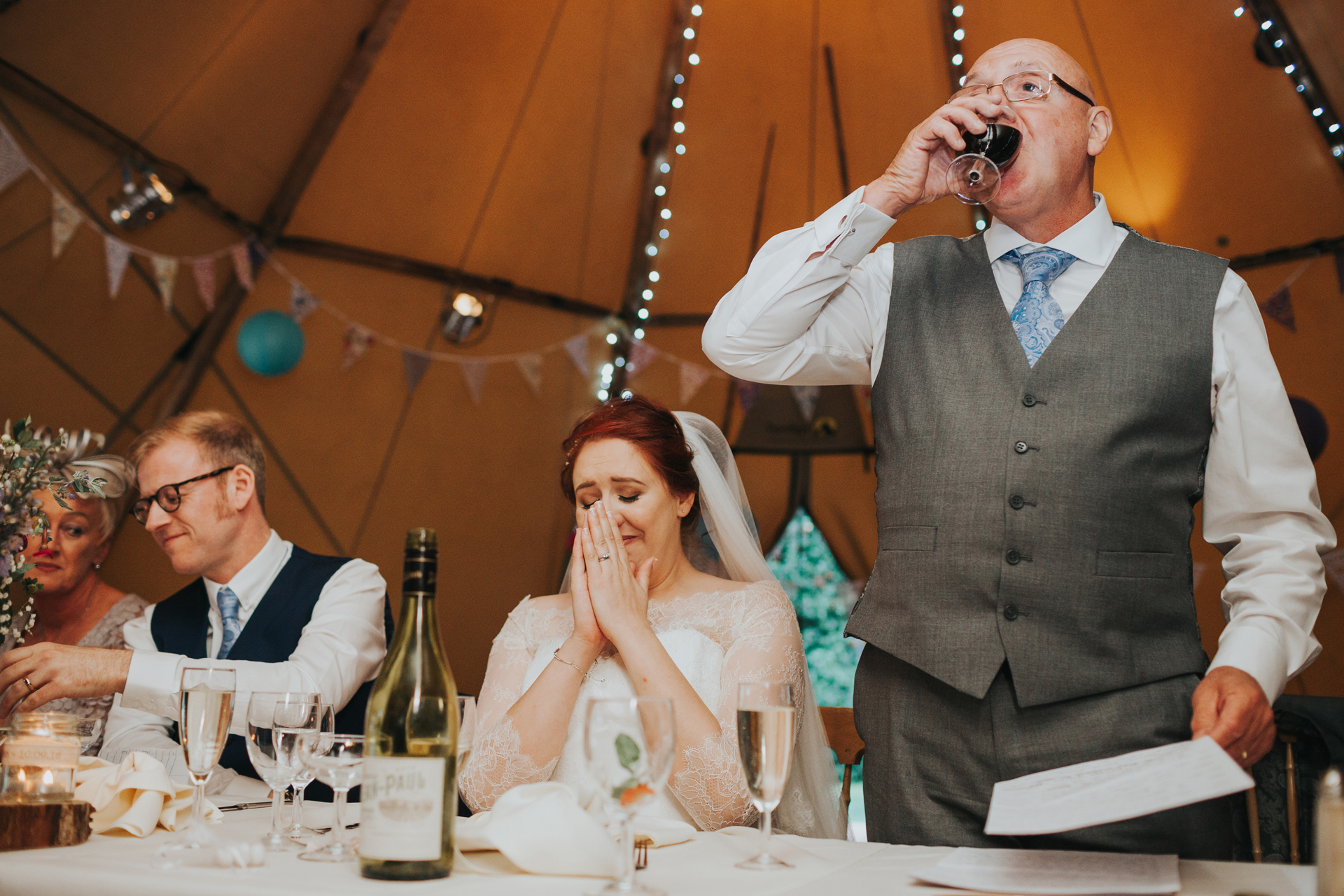 Father of the bride takes a drink, while the bride looks emotional.