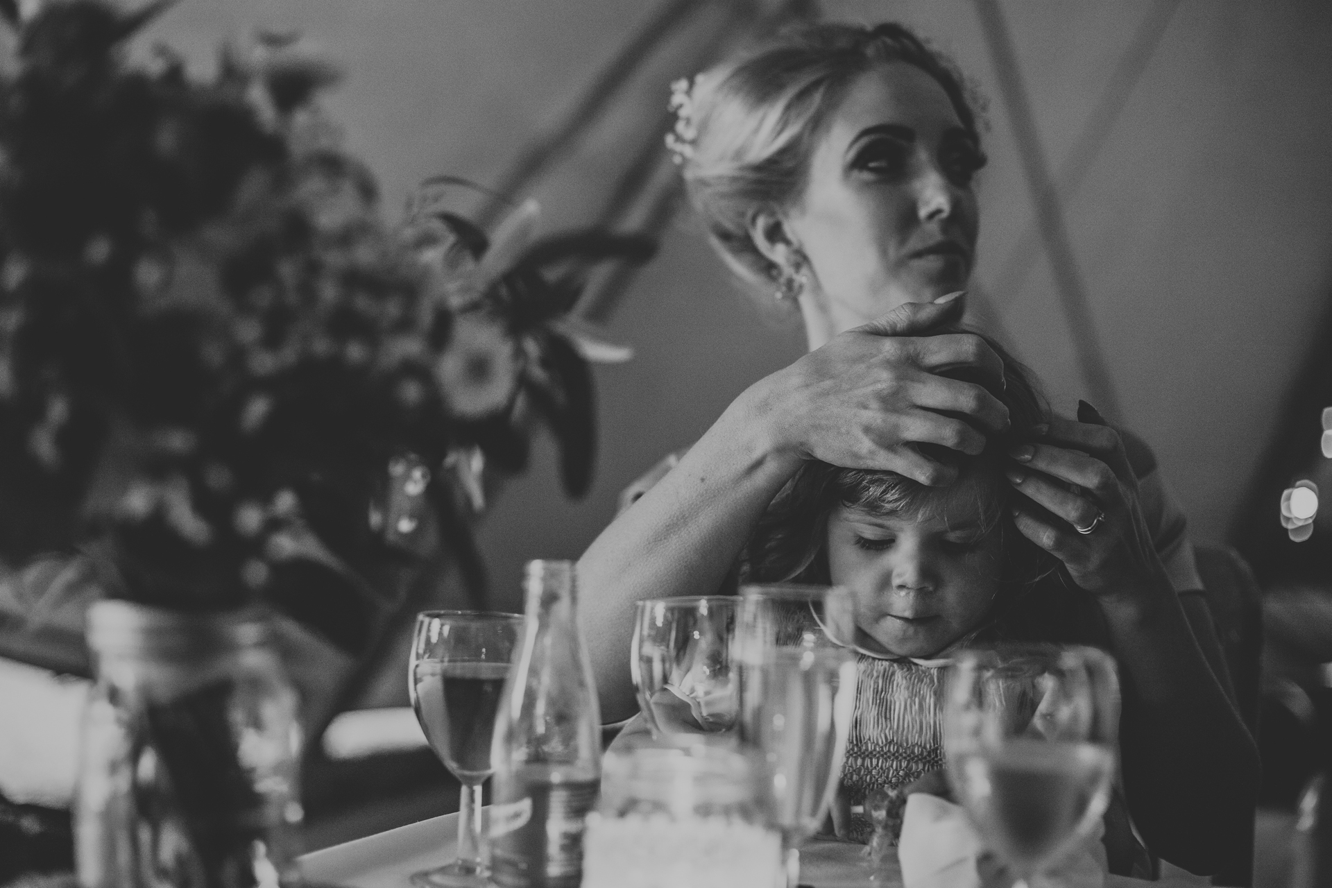 Bridesmaid plays with her daughters hair.