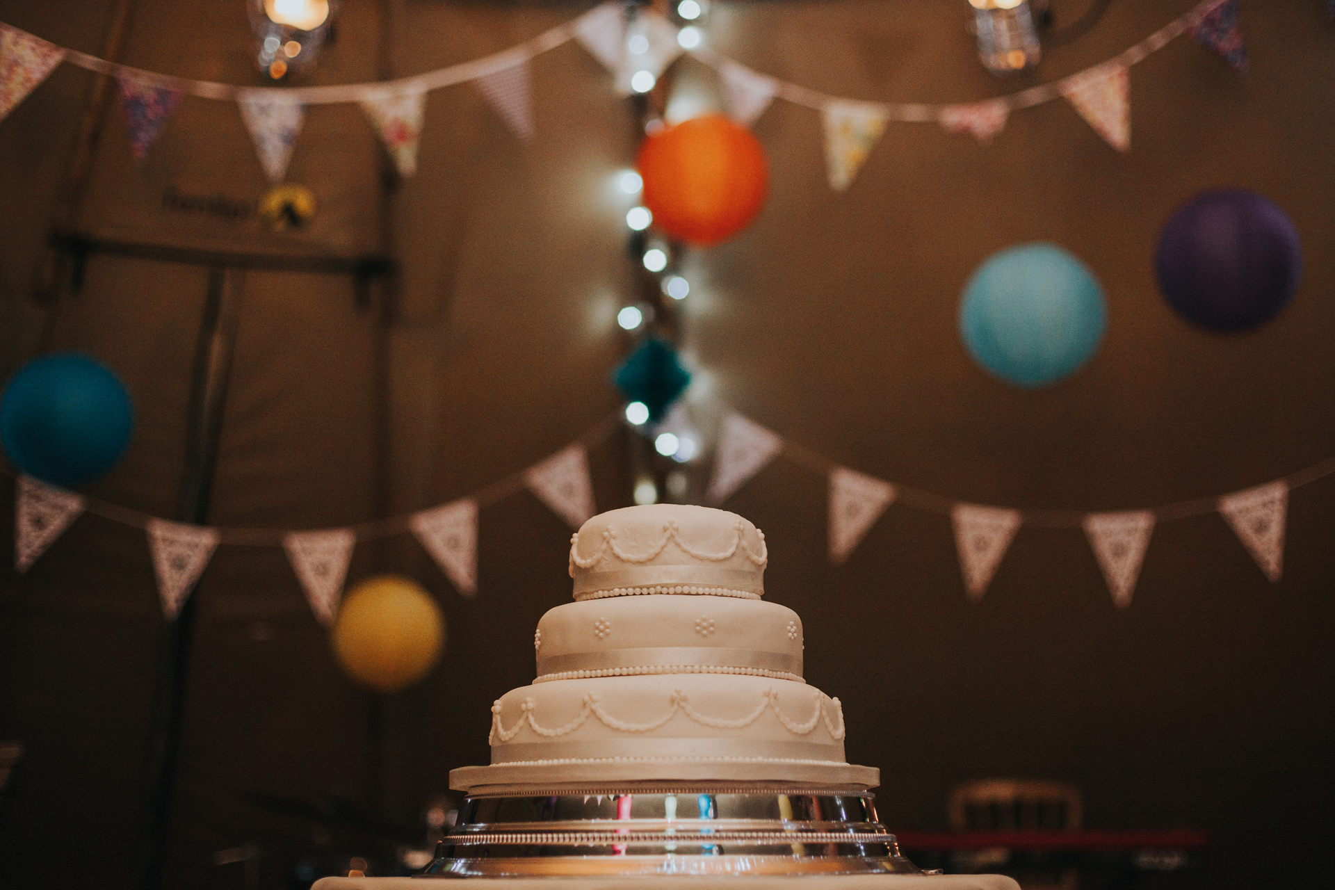 The wedding cake with bunting in background.