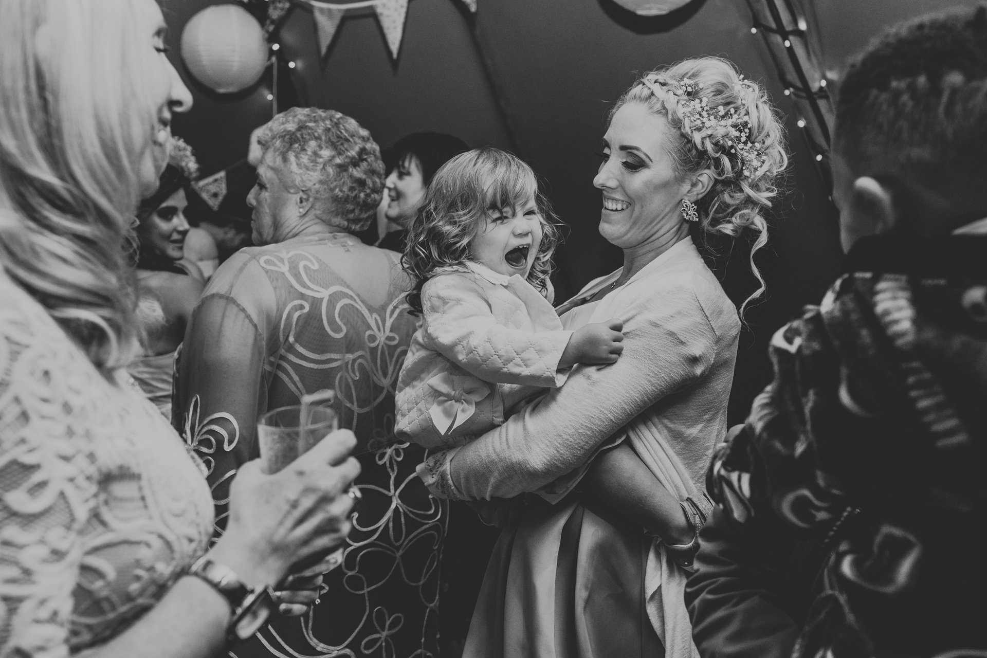 Bridesmaid dances with daughter.