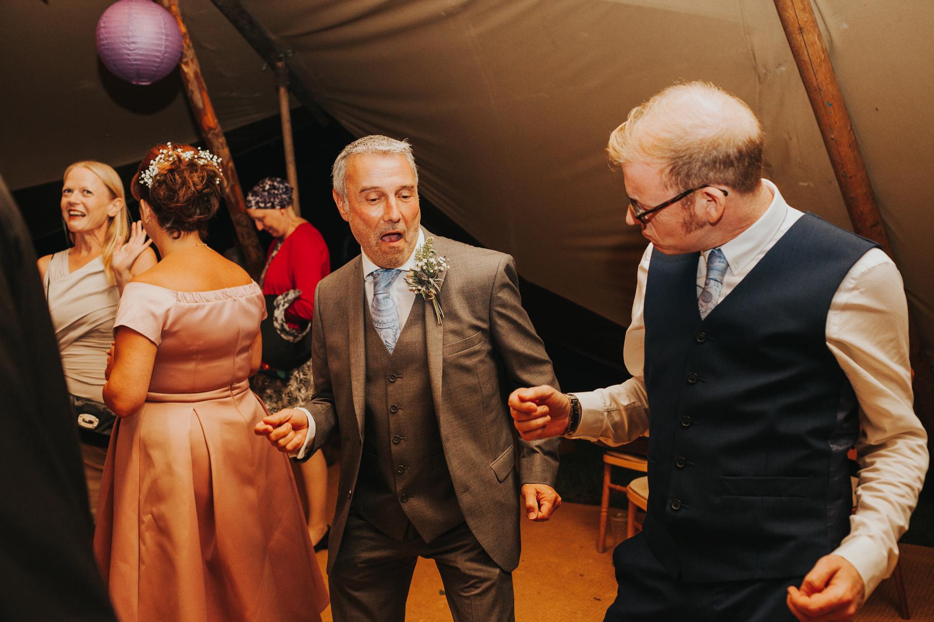 Groom and friend dancing.