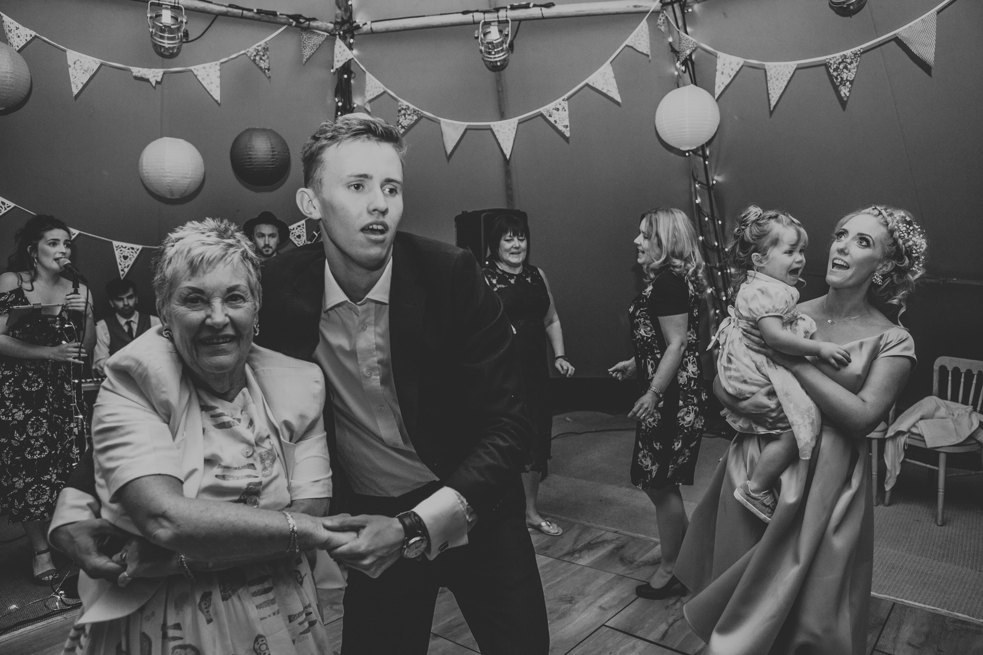 Guests dancing in tipi. Photo in black and white.