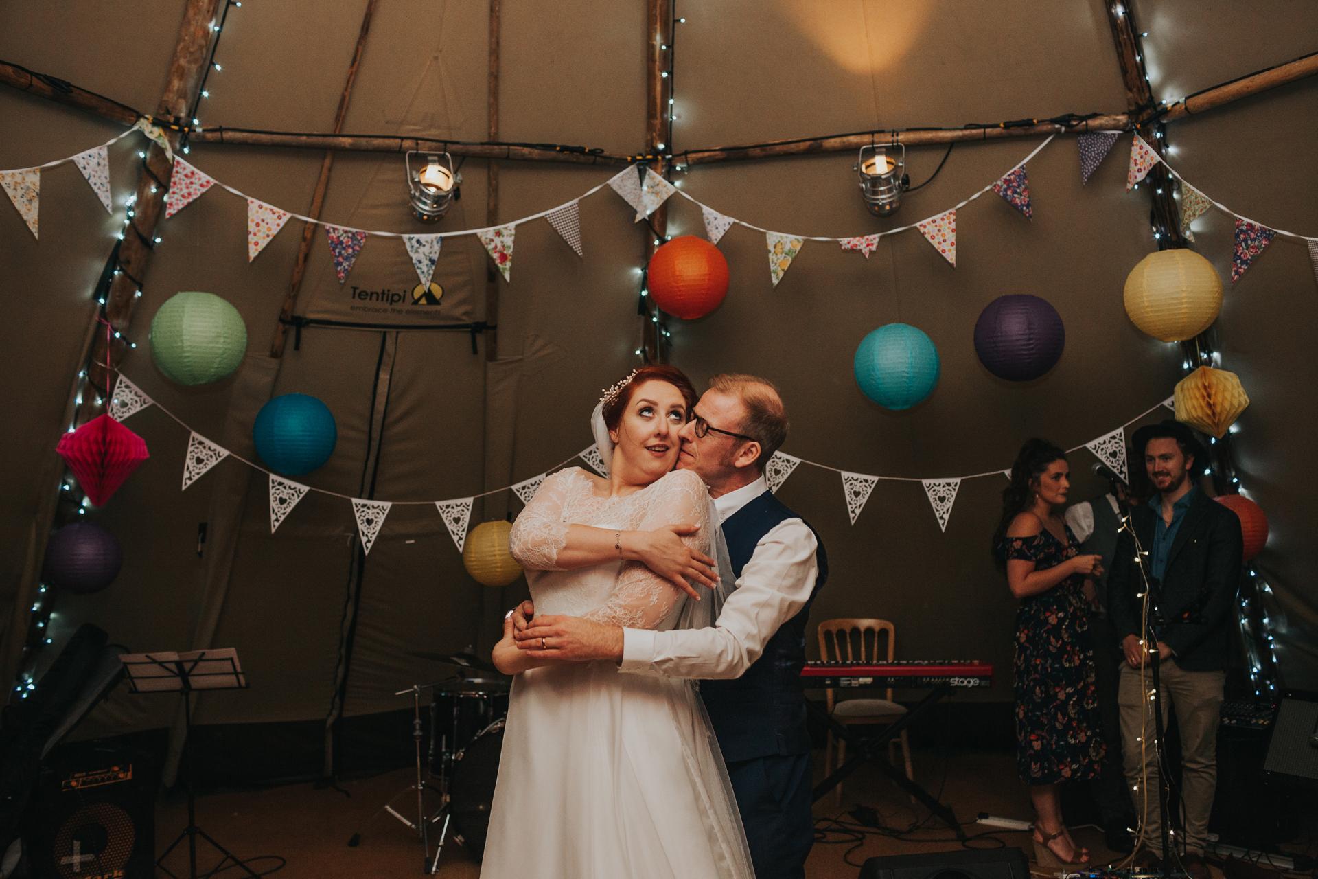 Bride and groom twirl and kiss on dance floor.