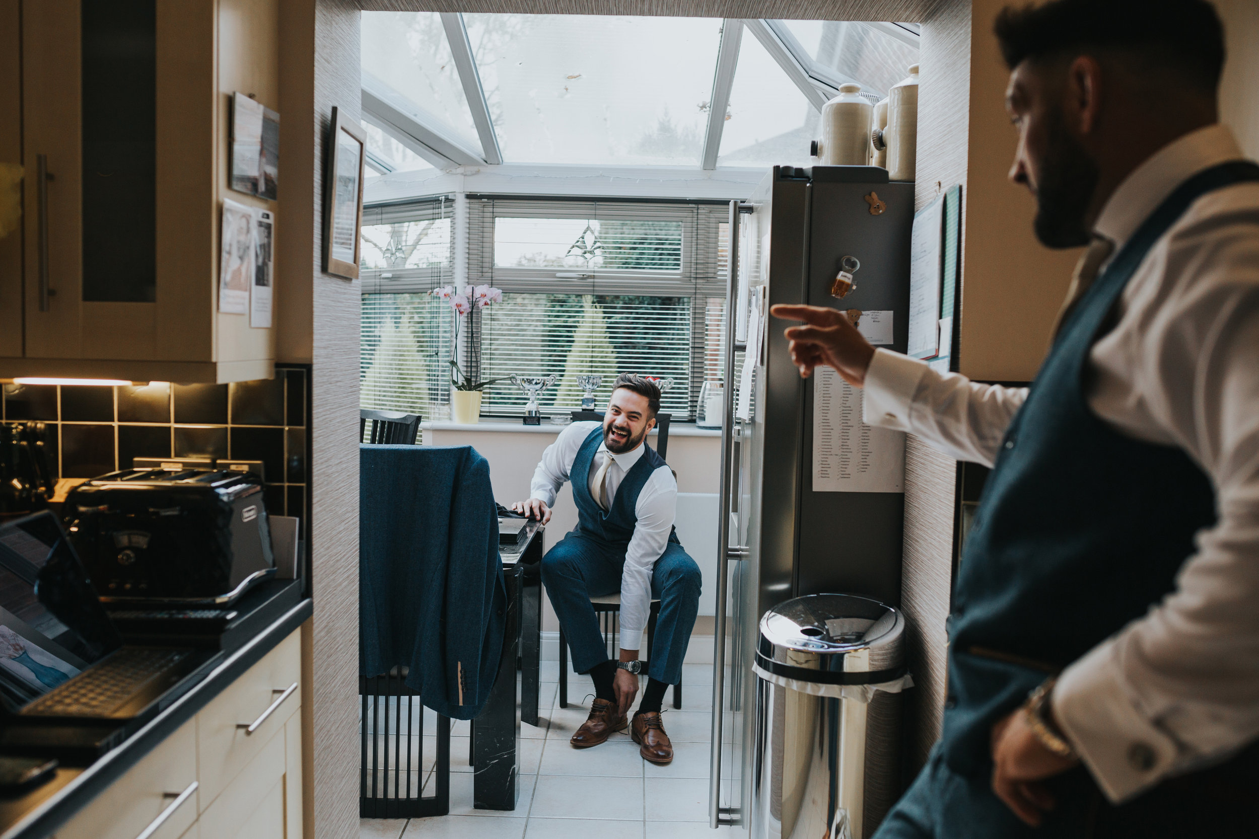 Groomsmen laughing together in the kitchen.
