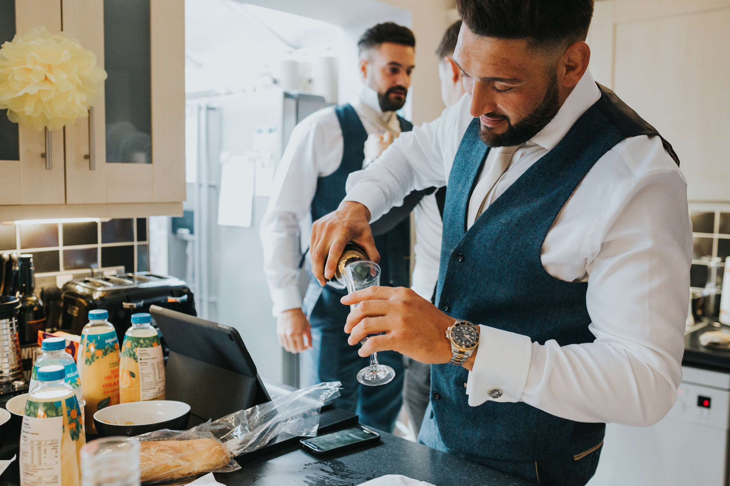Groomsman pouring a drink.