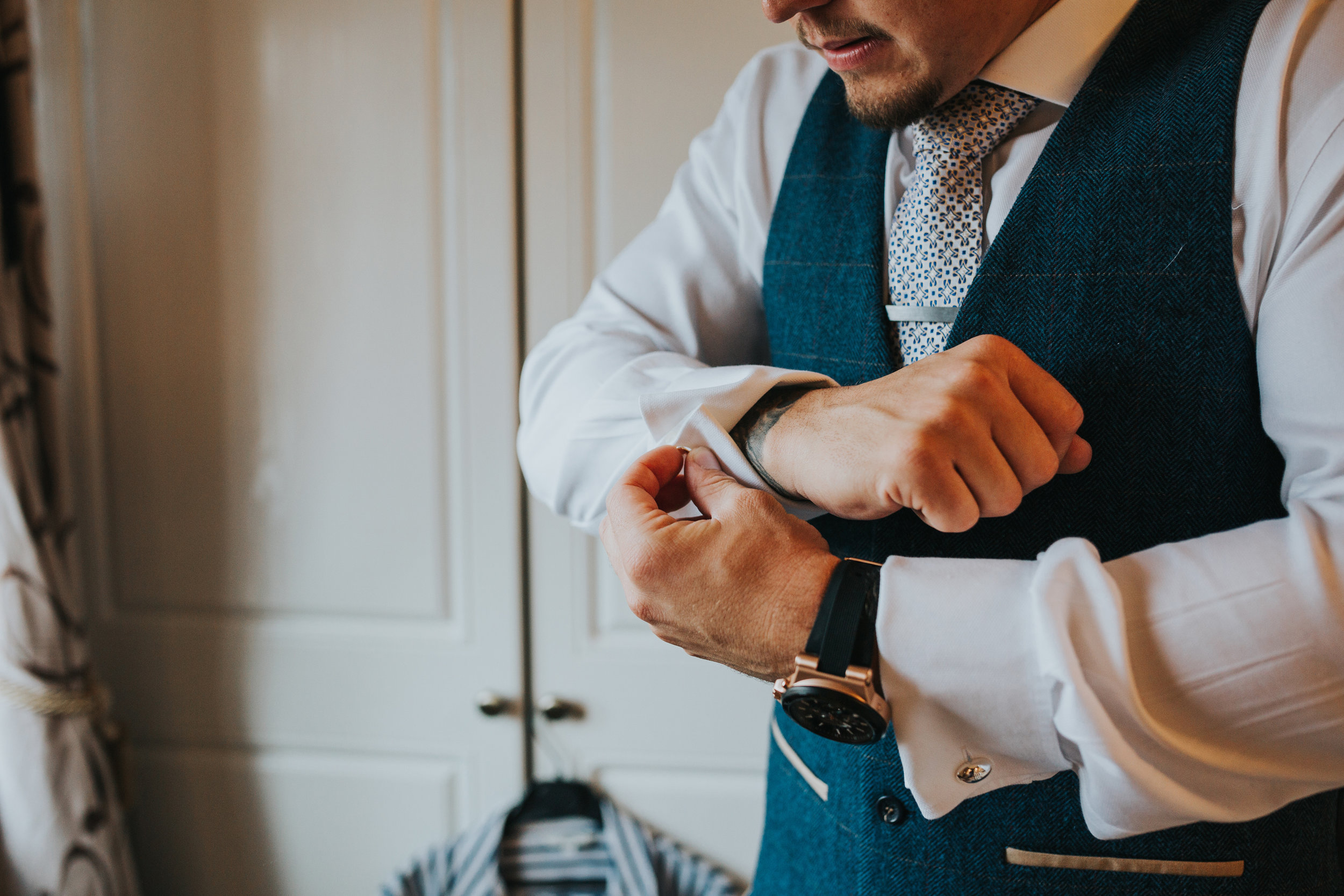 Groom putting on cuff links.